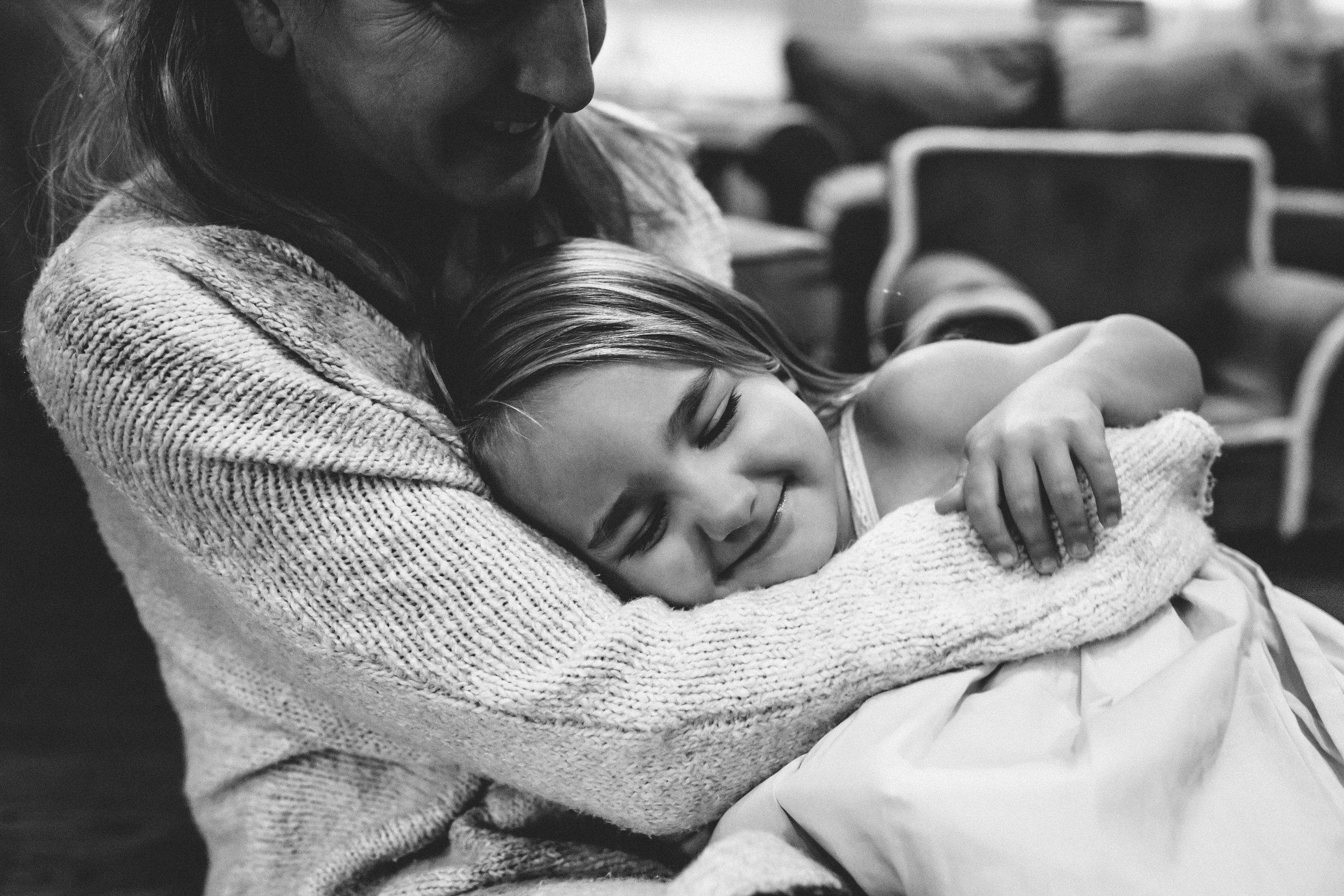 Mom hugging smiling daughter.