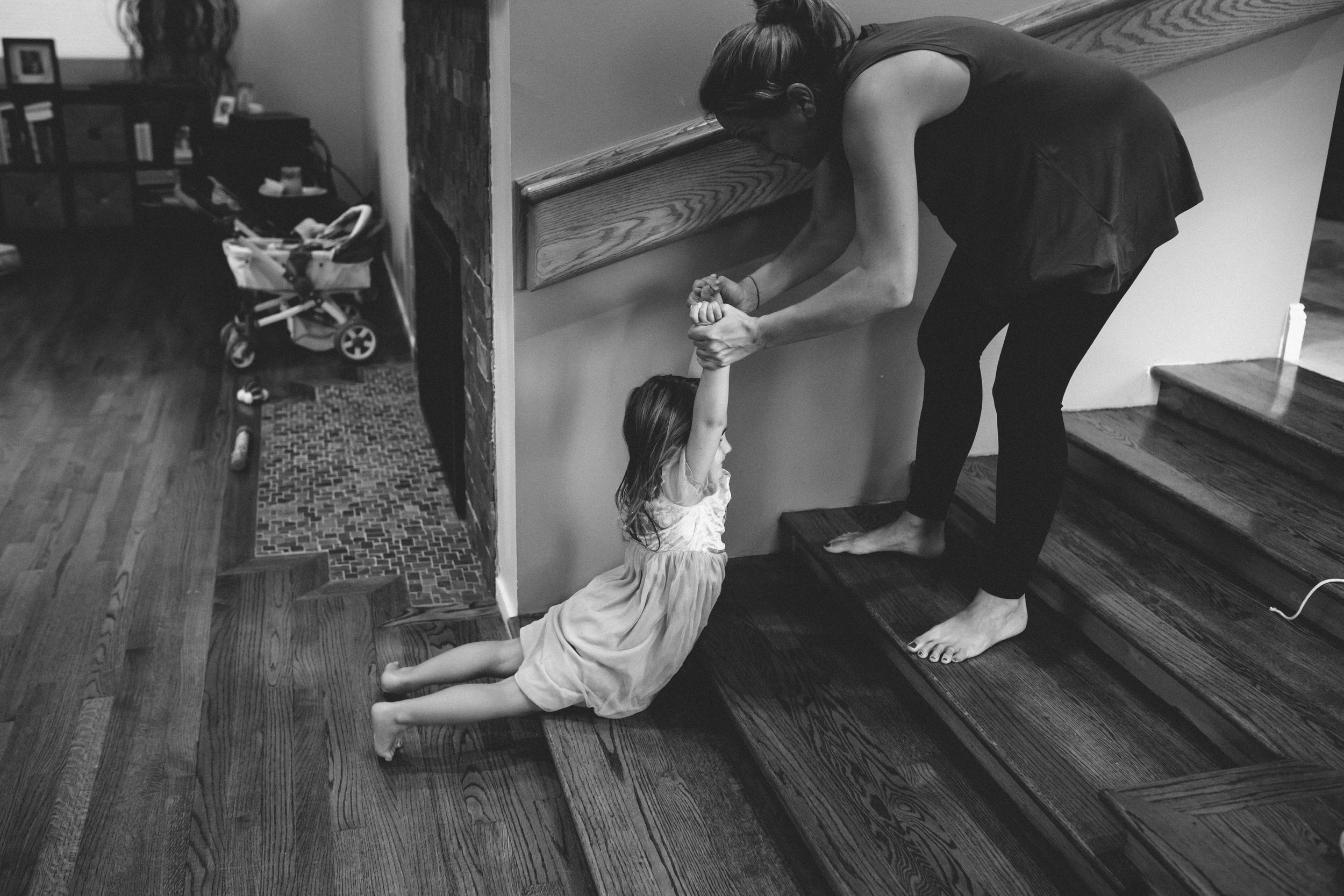 Mom pulling daughter up stairs.