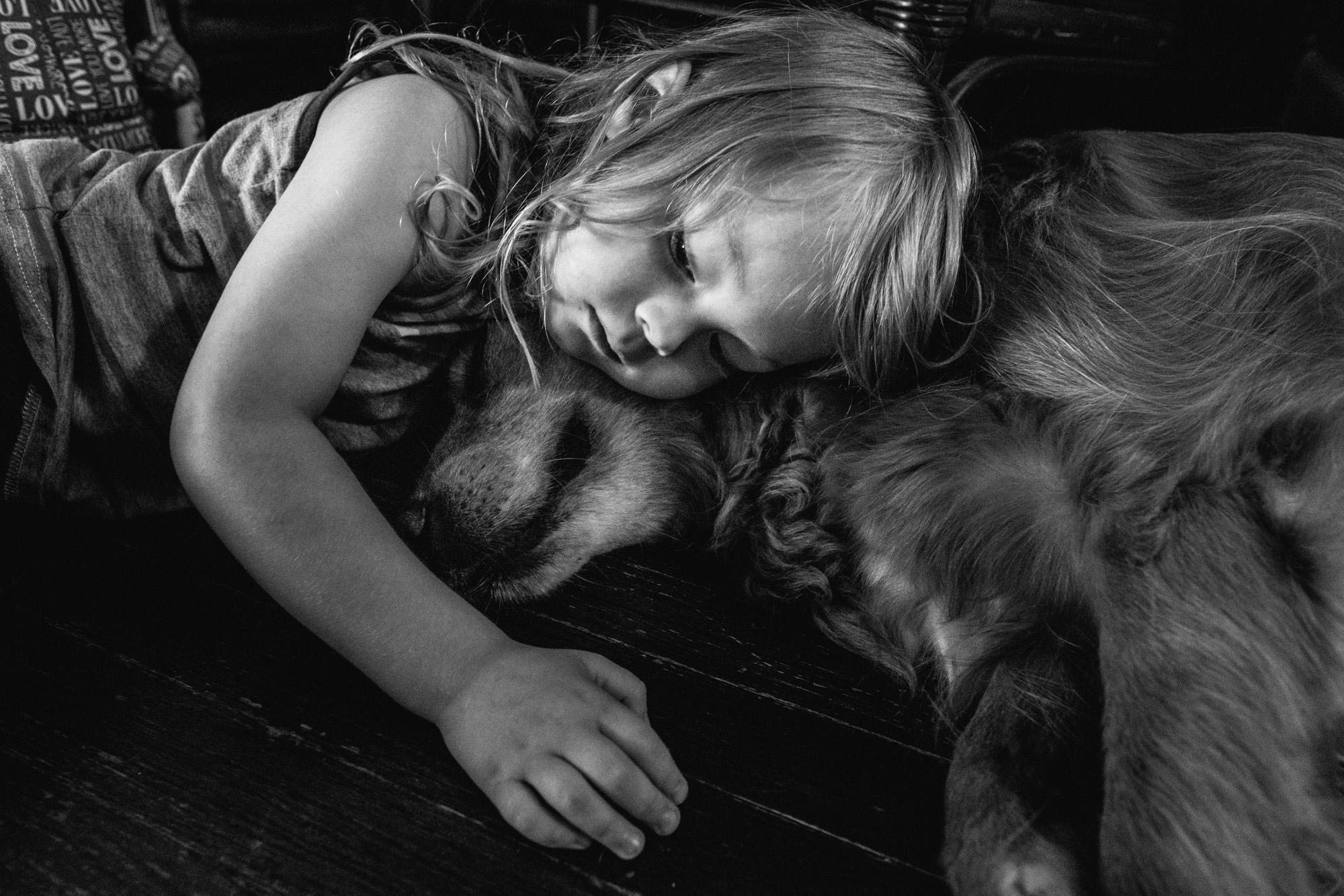 Boy cuddling with his dog.