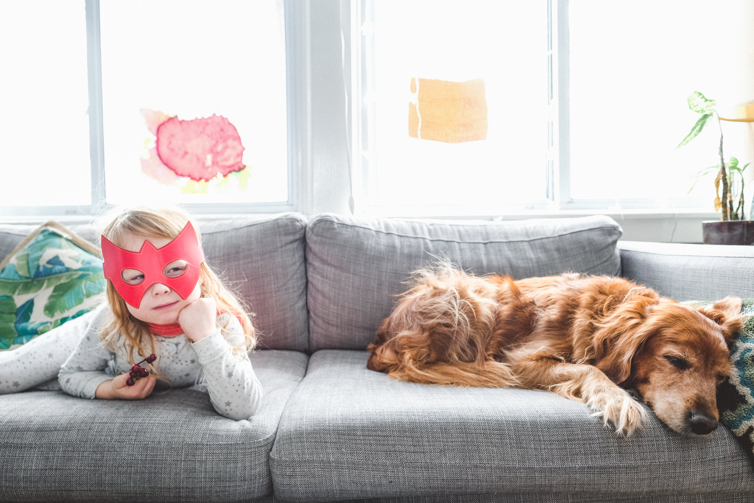 Kid in superhero mask sitting with his dog.
