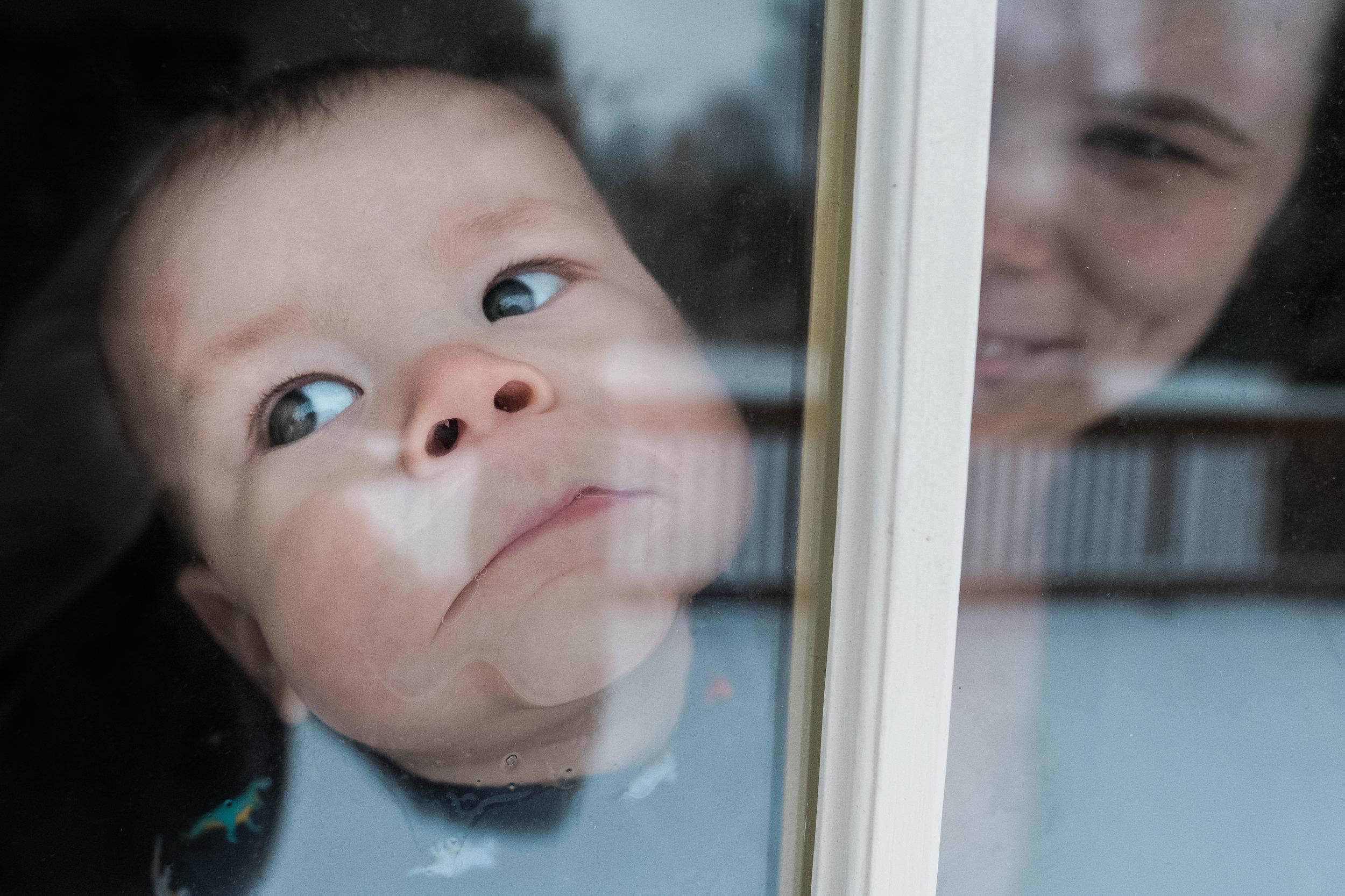 Baby smooshing face on window.