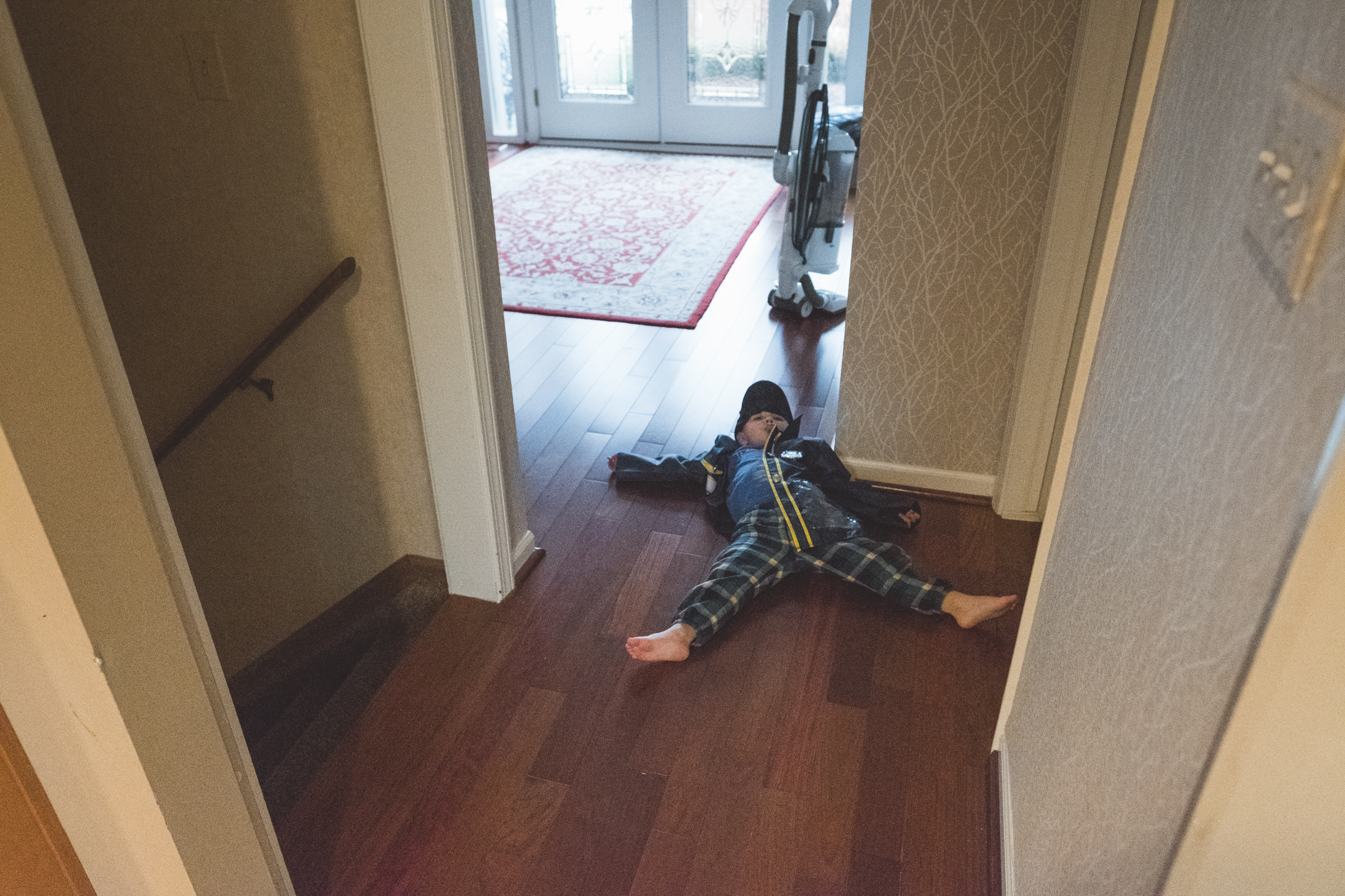 Boy lying on floor. Metro Detroit Ferndale Family Photographer