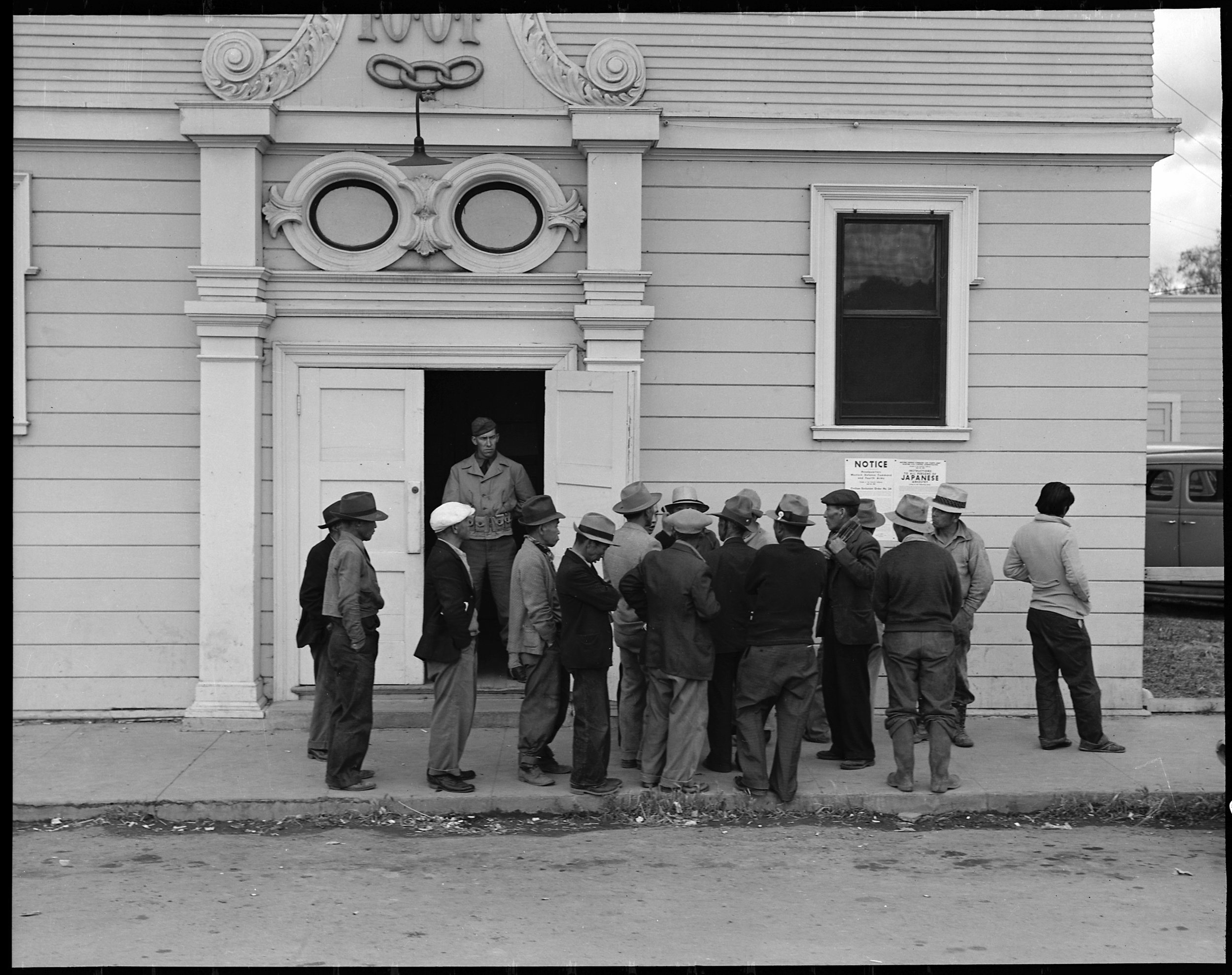 April 28, 1942 — Byron, California. Field laborers of Japanese ancestry from a large delta ranch have assembled at Wartime Civil Control Administration station to receive instructions for evacuation which is to be effective in three days under Civilian Exclusion Order Number 24. They are arguing together about whether or not they should return to the ranch to work for the remaining five days or whether they shall spend that time on their personal affairs.