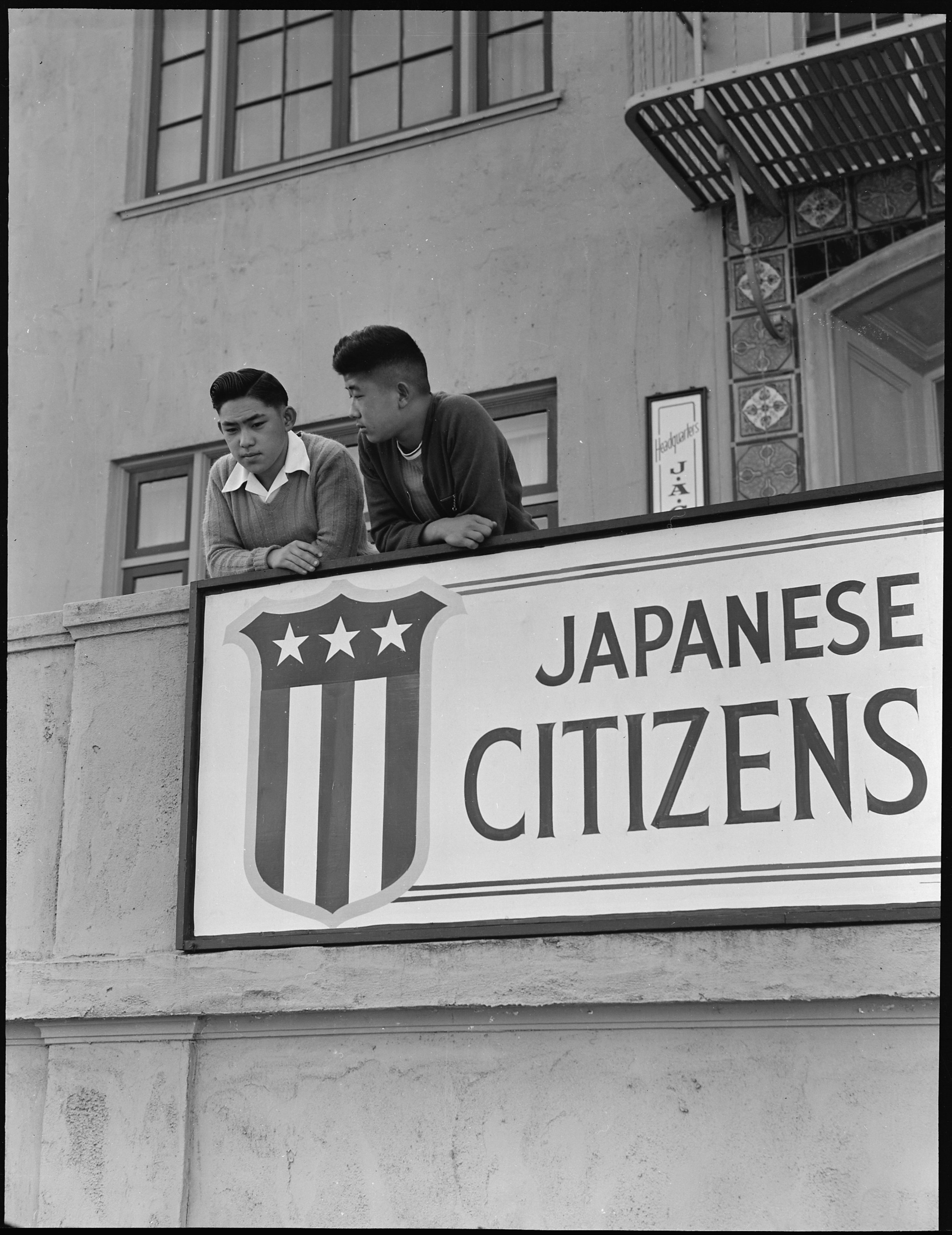 PRINT AVAILABLE   San Francisco, California. High school boys, on balcony of Japanese American Citizens League at 2031 Bush Street, look down sidewalk where friends boarded evacuation buses. Evacuees of Japanese ancestry will be housed in War Relocation Authority centers for the duration.