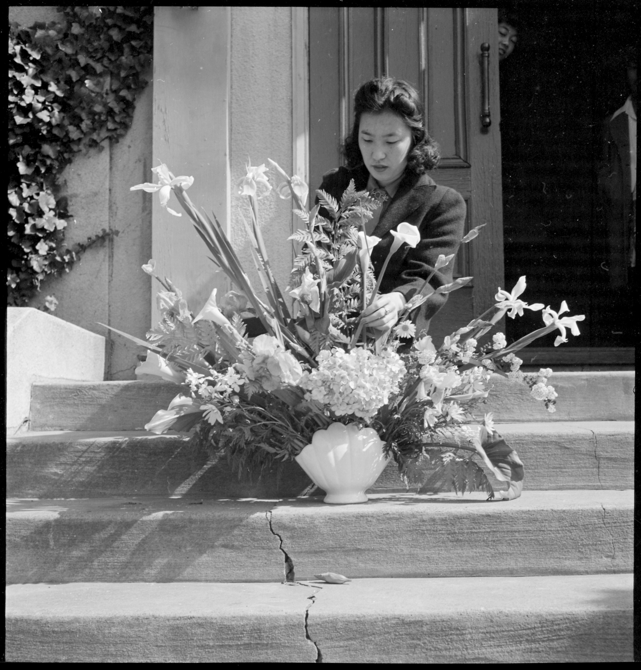 Oakland, California. Arranging flowers for altar on last day of service at Japanese Independent Congregational Church, prior to evacuation. Evacuees of Japanese ancestry will be housed at War Relocation Authority centers for the duration.