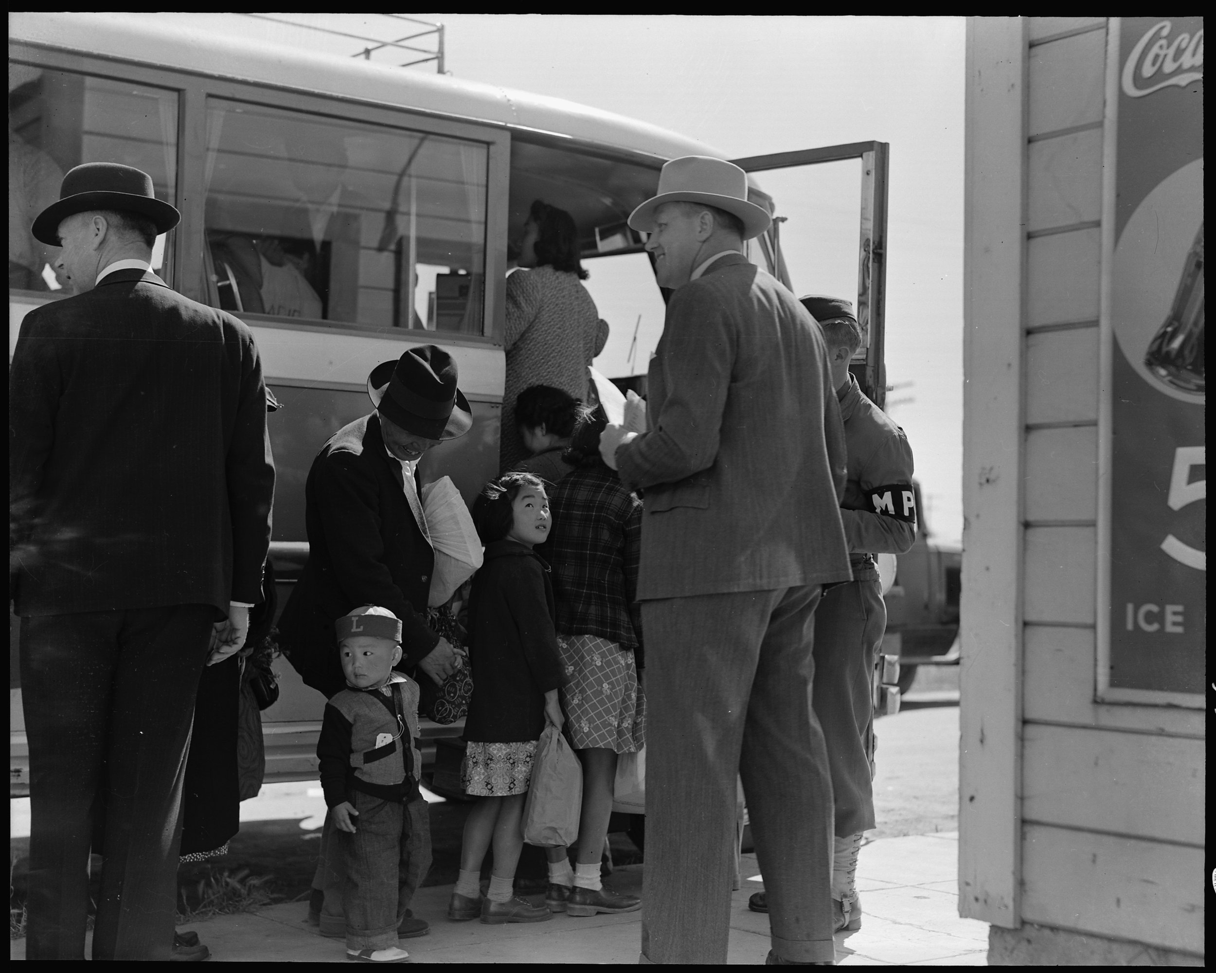 Byron, California. The bus which will take this farm family of Japanese ancestry to the Assembly center is almost ready to leave. Note identification tag on small boy.