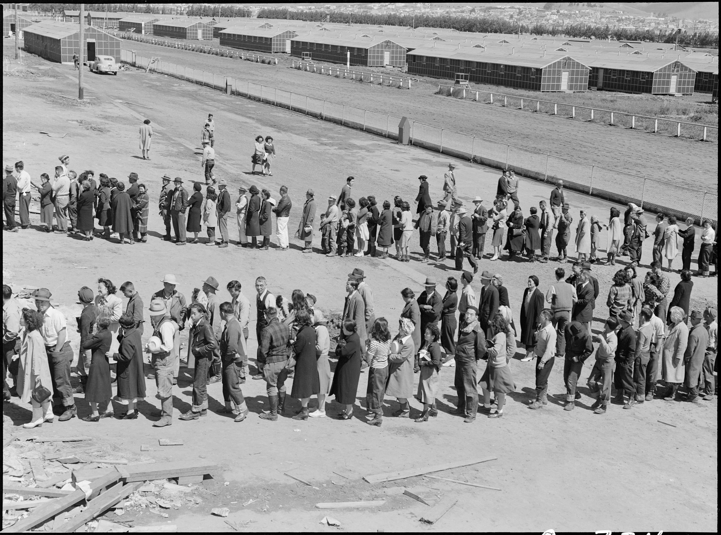 April 29, 1942 — San Bruno, California. This assembly center has been open for two days. Bus-load after bus-load of evacuated persons of Japanese ancestry are arriving on this day after going through the necessary procedures, they are guided to the quarters assigned to them in the barracks. Only one mess hall was operating today. Photograph shows line-up of newly arrived evacuees outside this mess hall at noon. Note barracks in background, just built, for family units. There are three types of quarters in the center of post office. The wide road which runs diagonally across the photograph is the former racetrack.