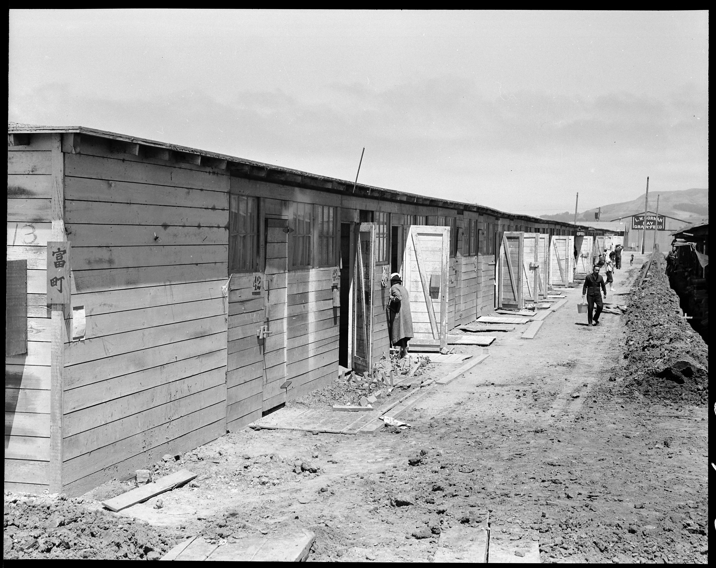 June 16, 1942 — San Bruno, California. This scene shows one type of barracks for family use. These were formerly the stalls for race horses. Each family is assigned to two small rooms, the inner one, of which, has no outside door nor window. The center has been in operation about six weeks and 8,000 persons of Japanese ancestry are now assembled here.