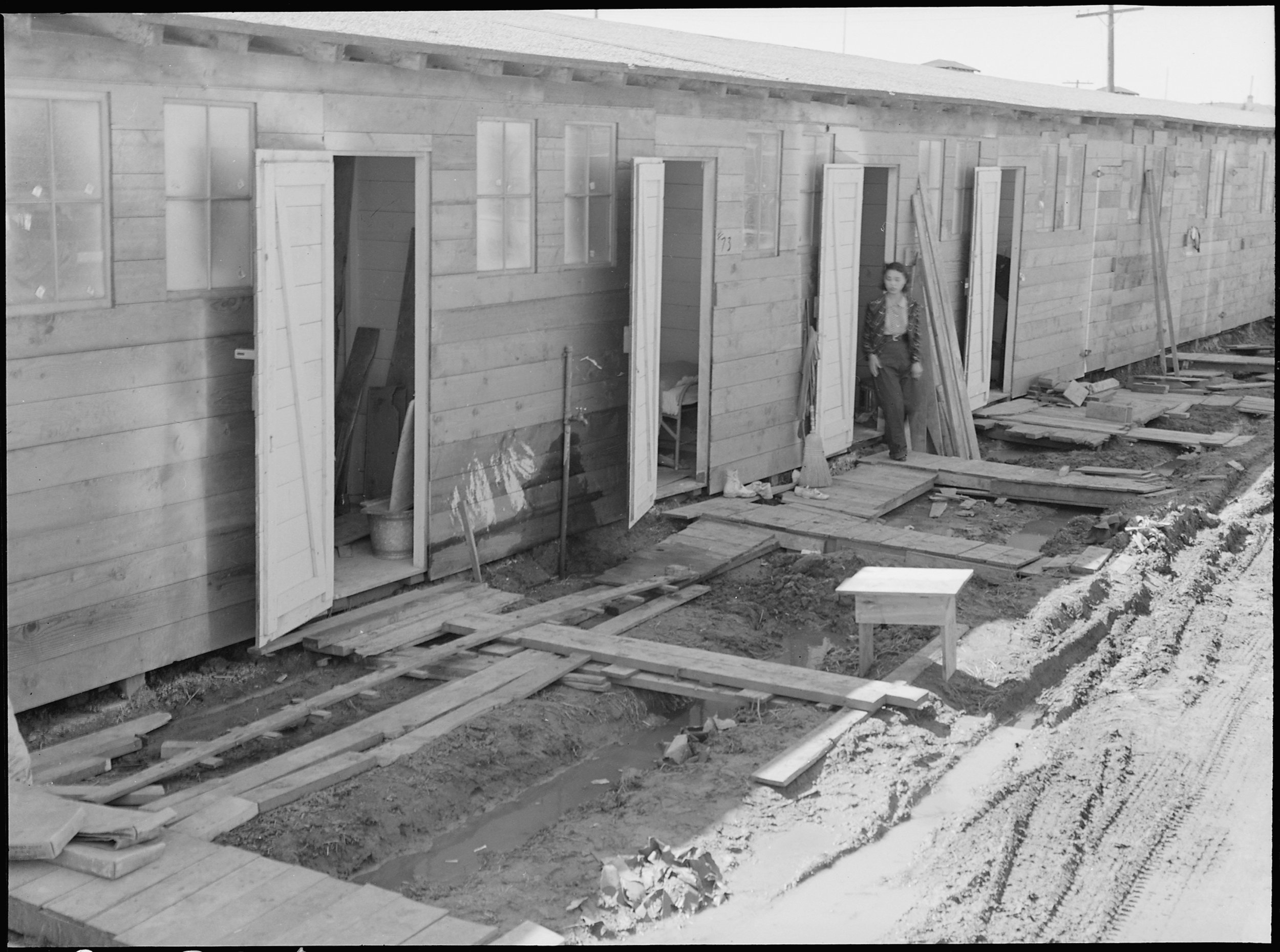 April 29, 1942 — Tanforan Assembly center, San Bruno, California. Barracks for family living quarters. Each door enters into a family unit of two small rooms. Tanforan assembly center was opened two days before the photograph was made. On the first day there had been a heavy rain. When a family has arrived here, first step of evacuation is complete.