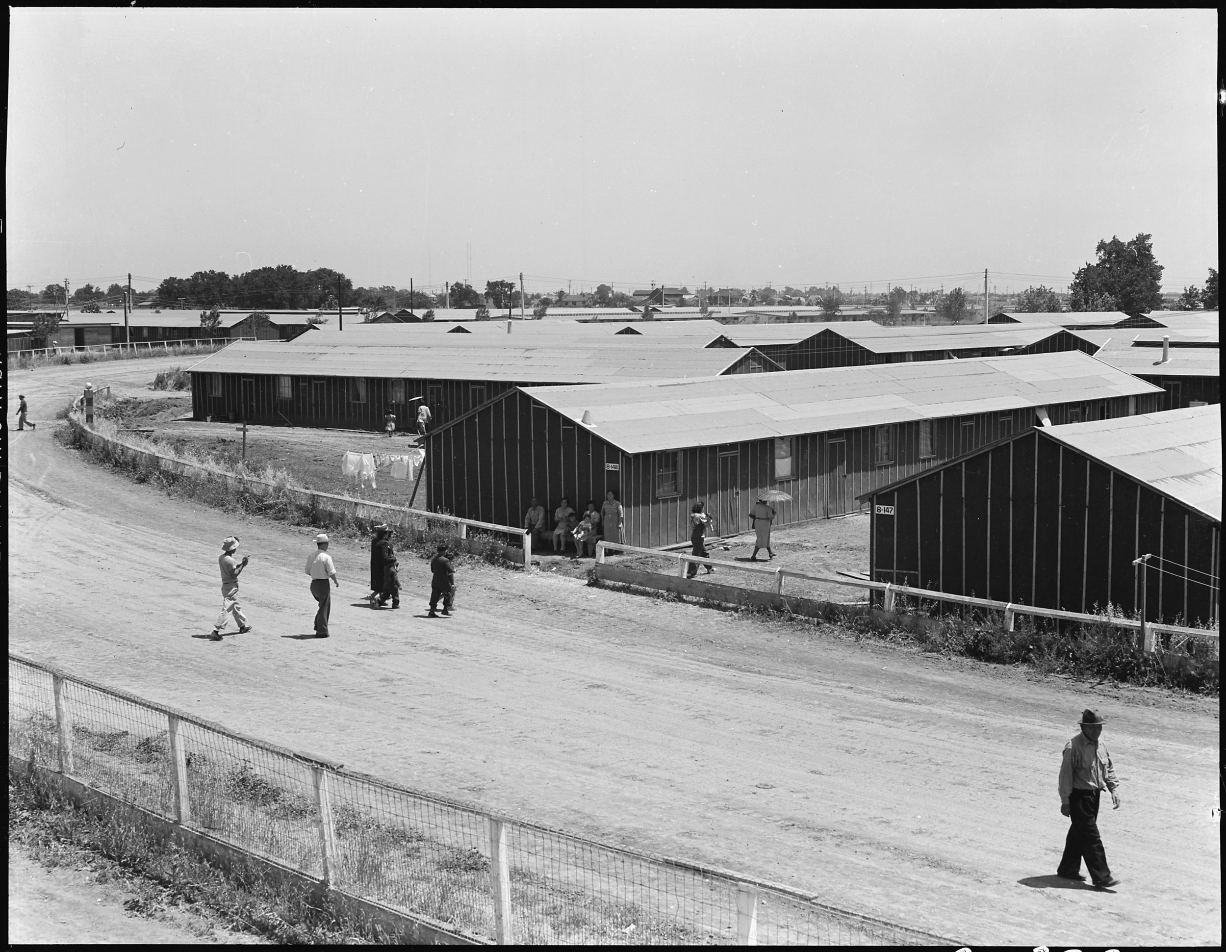 May 19, 1942 — Stockton, California. Noon on a hot day at the Stockton Assembly center, which is a converted fairgrounds. This photograph shows the old race track. This center has been opened a week and evacuees will arrive daily until the capacity of 5000 is reached.