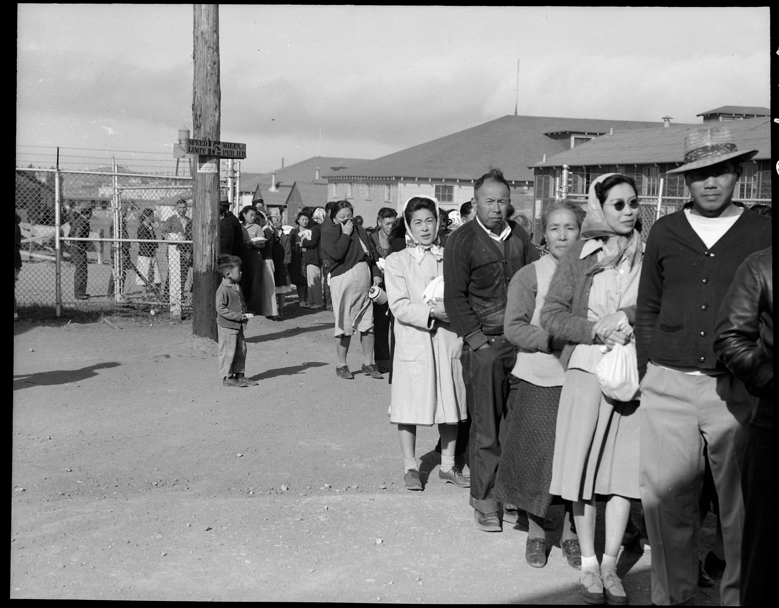 """June 16, 1942 — San Bruno, California. Supper time! Meal times are the big events of the day within an assembly center. This is a line-up of evacuees waiting for the """"B"""" shift at 5:45 pm. They carry with them their own dishes and cutlery in bags to protect them from the dust. They, themselves, individually wash their own dishes after each meal, since dish washing facilities in the mess halls proved inadequate. Most of the residents prefer this second shift because they sometimes get second helpings, but the groups are rotated each week. There are eighteen mess halls in camp which, together, accomodate 8,000 persons three times a day. All food is prepared and served by evacuees."""