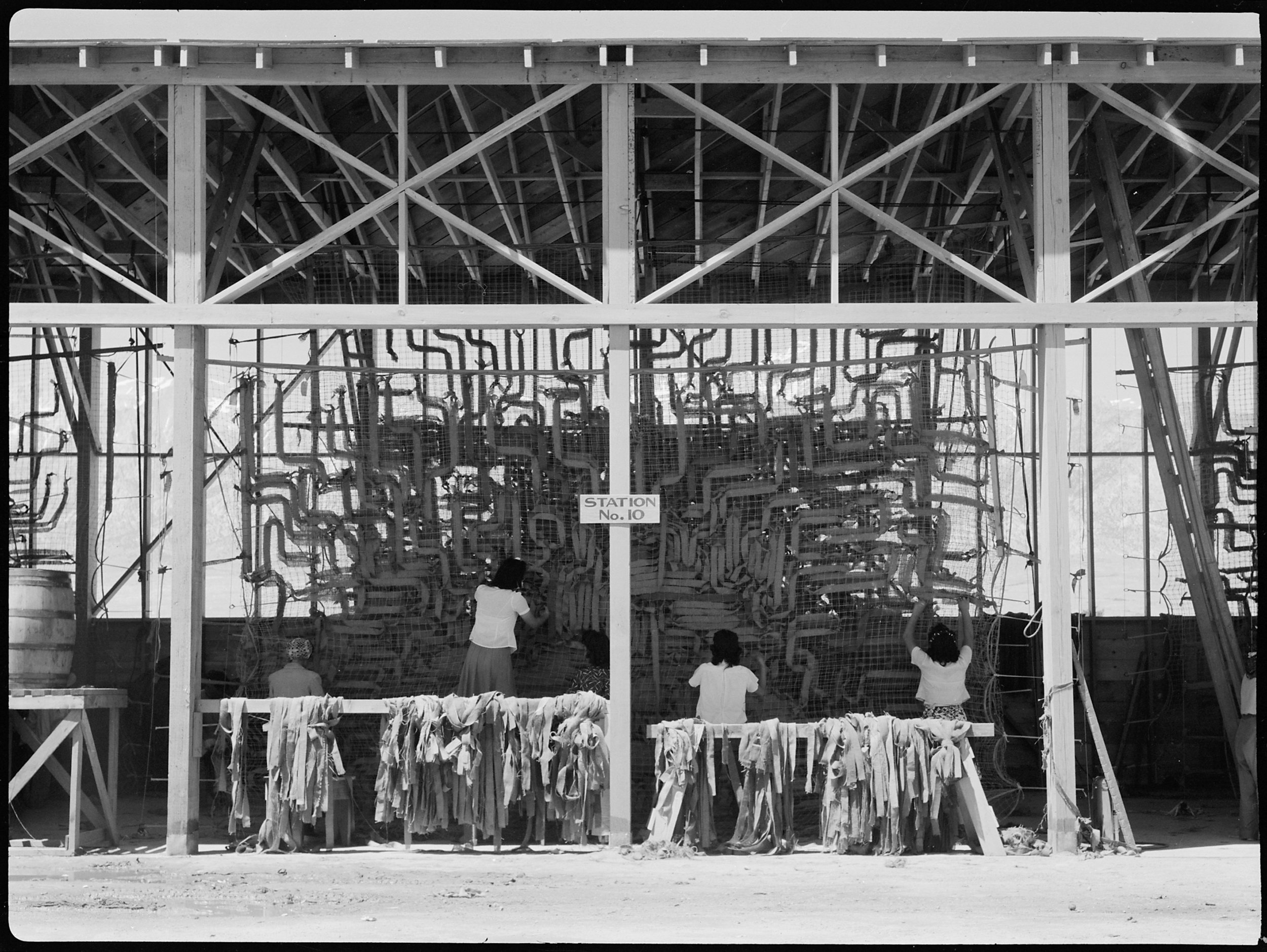 PRINT AVAILABLE   July 1, 1942 — Manzanar Relocation Center, Manzanar, California. Making camouflage nets for the War Department. This is one of several War and Navy Department projects carried on by persons of Japanese ancestry in relocation centers.