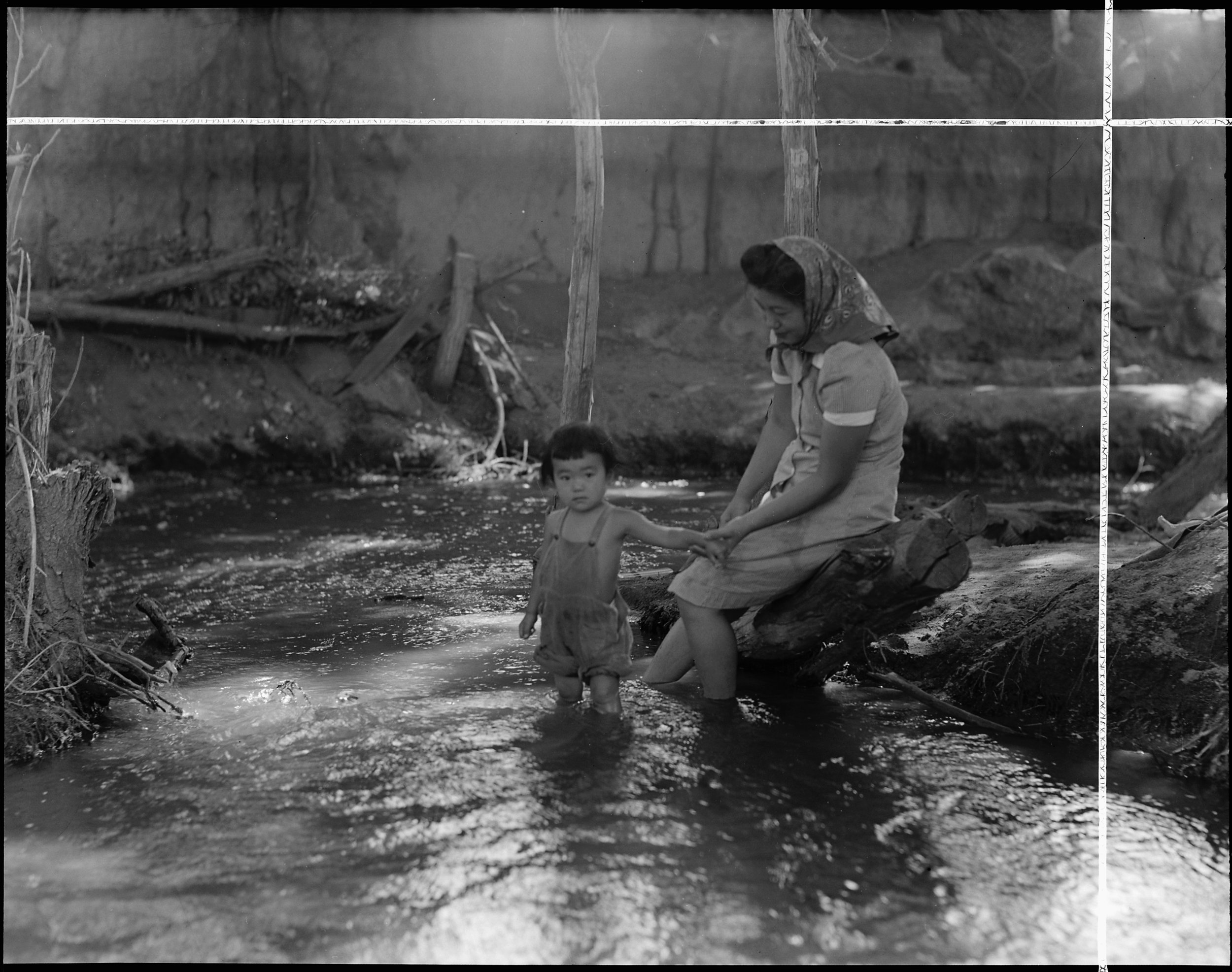 Manzanar Relocation Center, Manzanar, California. Evacuees enjoying the creek which flows along the outer border of this War Relocation Authority center.