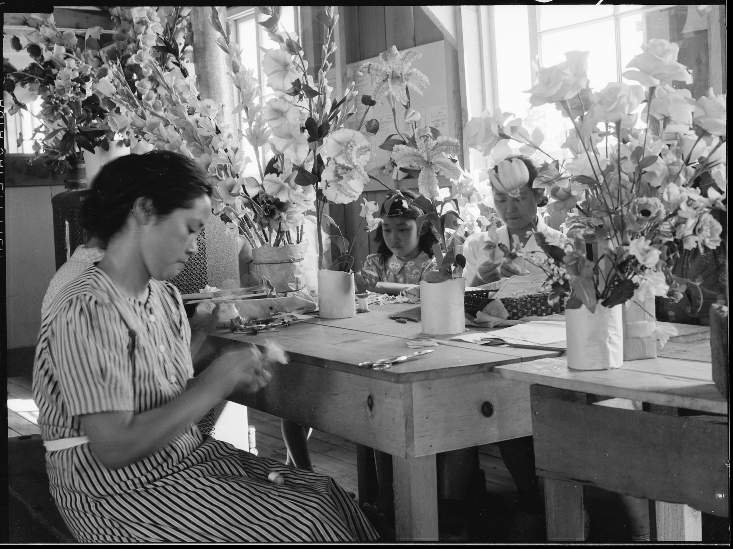 PRINT AVAILABLE   Manzanar Relocation Center, Manzanar, California. Making artificial flowers in the Art School at this War Relocation Authority center for evacuees of Japanese ancestry.