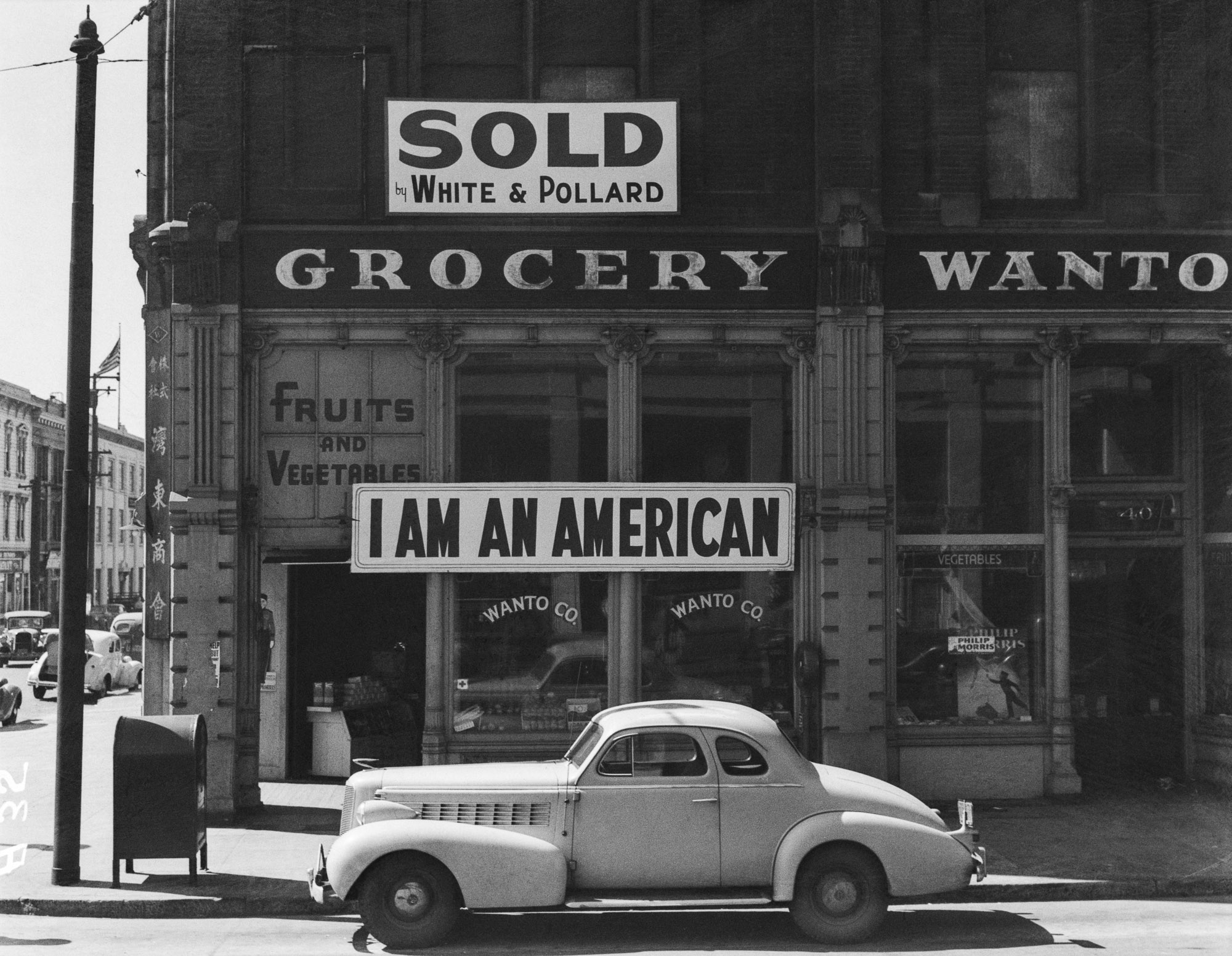 """PRINT AVAILABLE   Oakland, Calif., Mar. 1942. A large sign reading """"I am an American"""" placed in the window of a store, at 13th and Franklin streets, on December 8, the day after Pearl Harbor. The store was closed following orders to persons of Japanese descent to evacuate from certain West Coast areas. The owner, a University of California graduate, will be housed with hundreds of evacuees in War Relocation Authority centers for the duration of the war"""