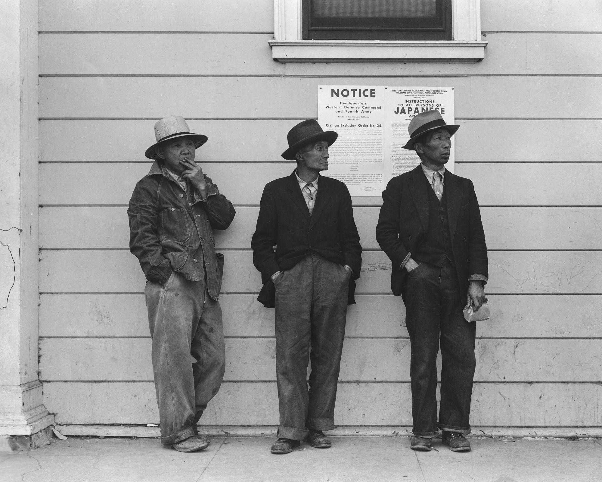 PRINT AVAILABLE   April 28, 1942 — Byron, California. Field laborers of Japanese ancestry in front of Wartime Civil Control Administration station where they have come for instructions and assistance in regard to their evacuation due in three days under Civilian Exclusion Order Number 24. This order affects 850 persons in this area. The men are now waiting for the truck which will take them, with the rest of the field crew, back to the large-scale delta ranch.