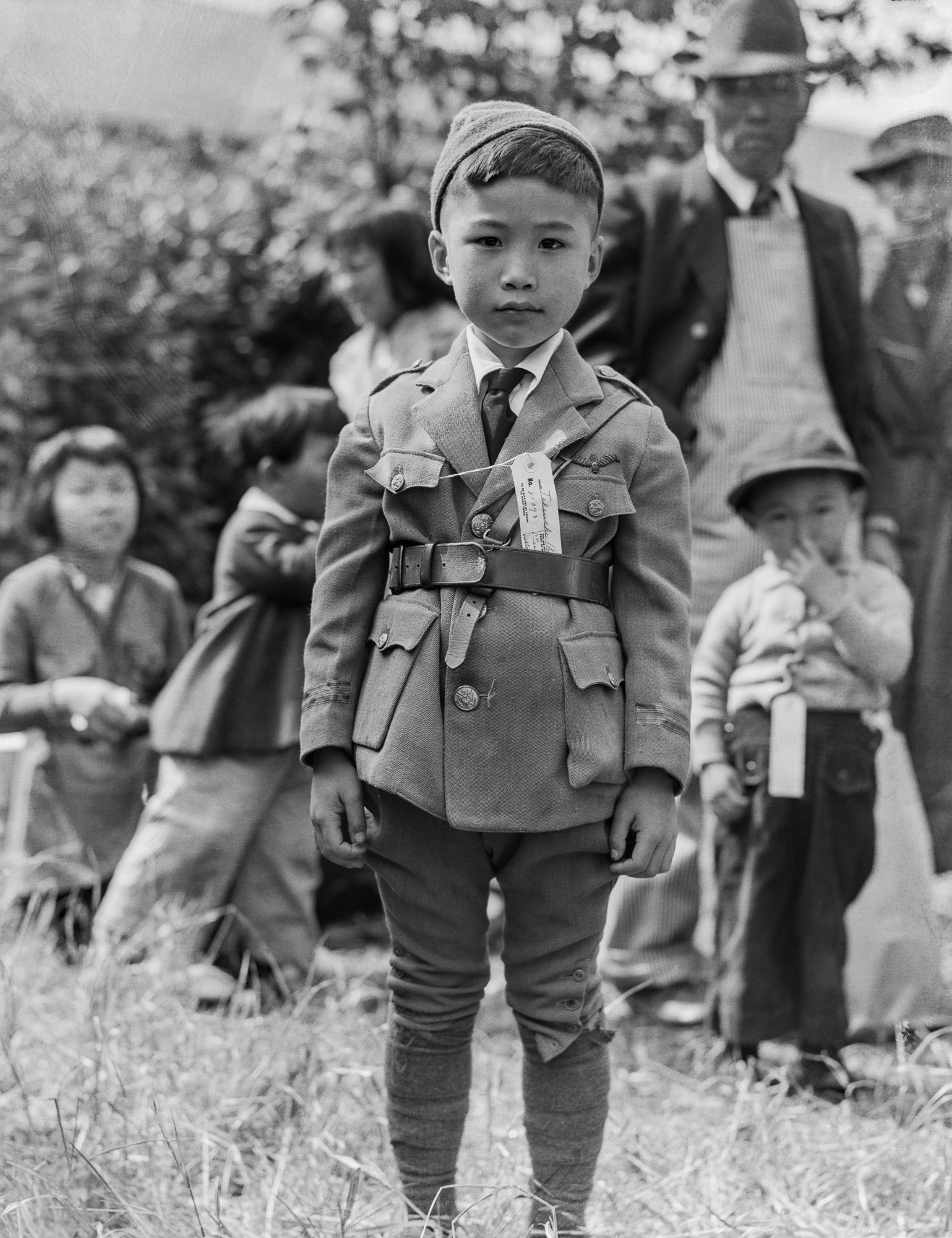 PRINT AVAILABLE   May 9, 1942 — Centerville, California. This youngster is awaiting evacuation bus. Evacuees of Japanese ancestry will be housed in War Relocation Authority centers for the duration.