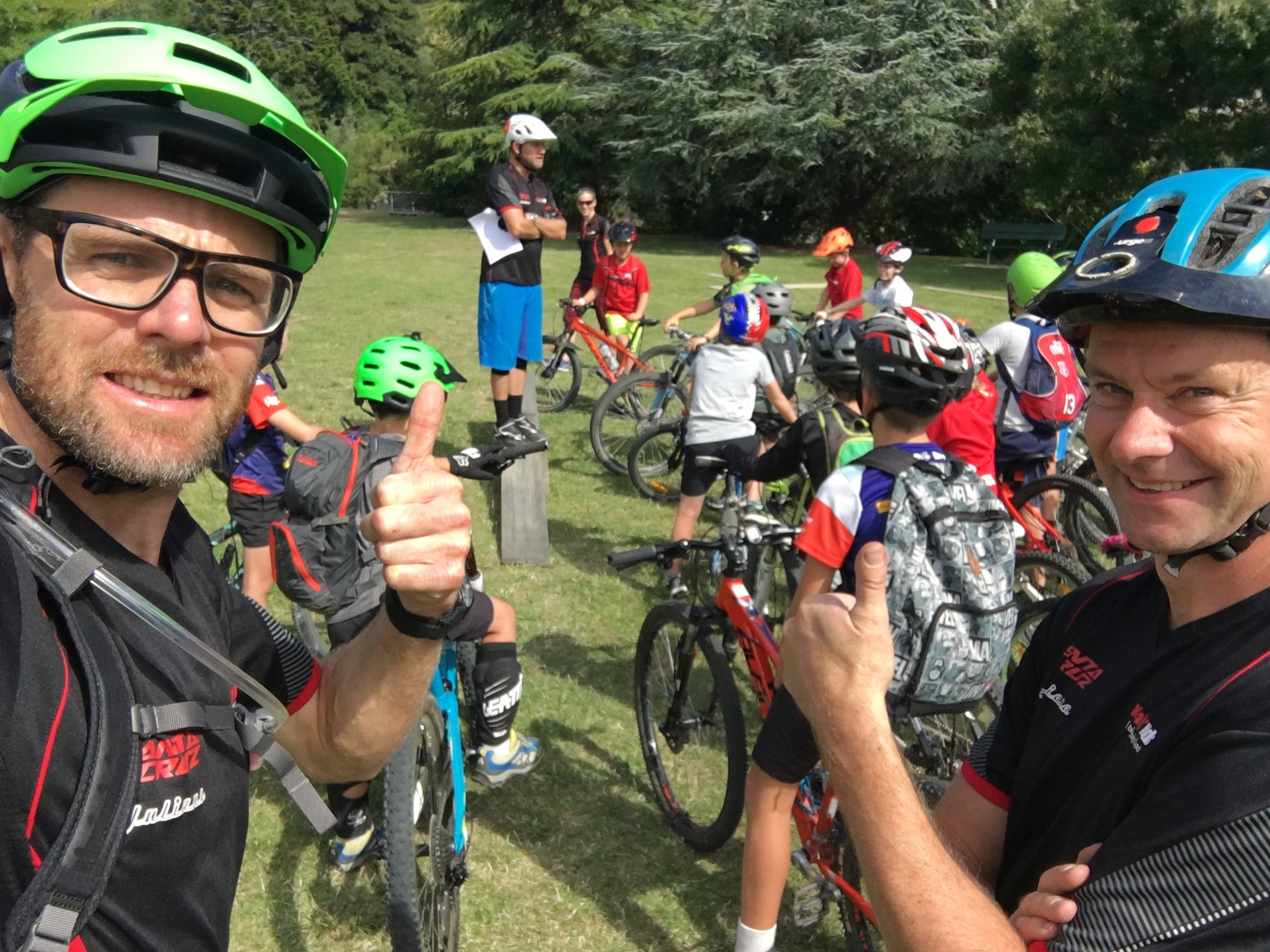 Coaches Damian Stones (mountain bike adventurer) and Mike Anderson (local bike shop owner) take a checkie selfie while Tay does roll call.