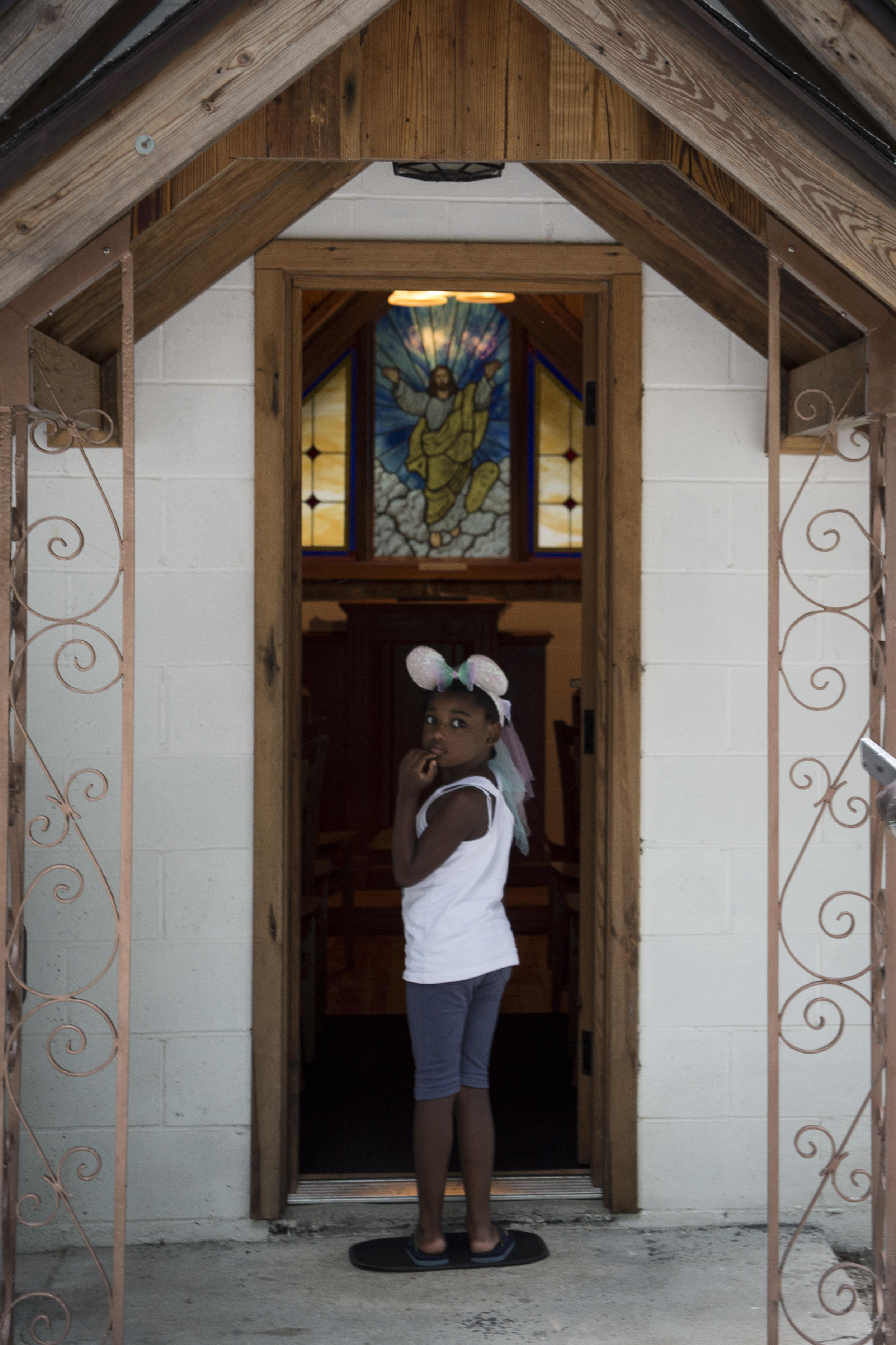 A little girl visiting the church looks back at her father before entering.