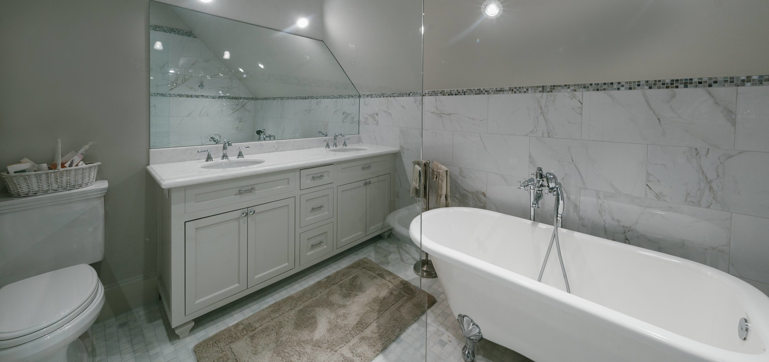 The view from the walk in shower shows the free standing clawfoot bathtub, the custom cabinets and the clean white marble countertops. Even though simple, this guest bathroom is a place of elegance and truly an escape for each guest.