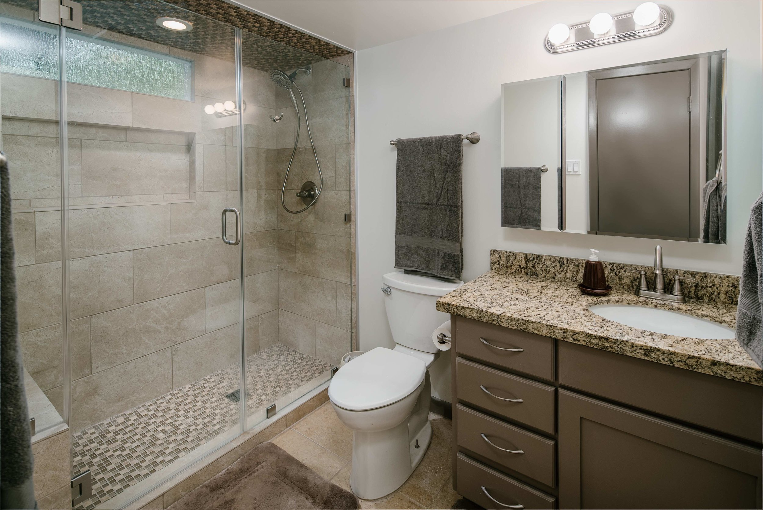 The beauty of this bathroom comes from the gorgeous granite countertops, the custom cabinets, and the simple yet elegant tile. What makes it unique however is the shower design. This shower is a long shampoo niche, frameless glass doors, and a tile rug on the floor that is mirrored on the ceiling.