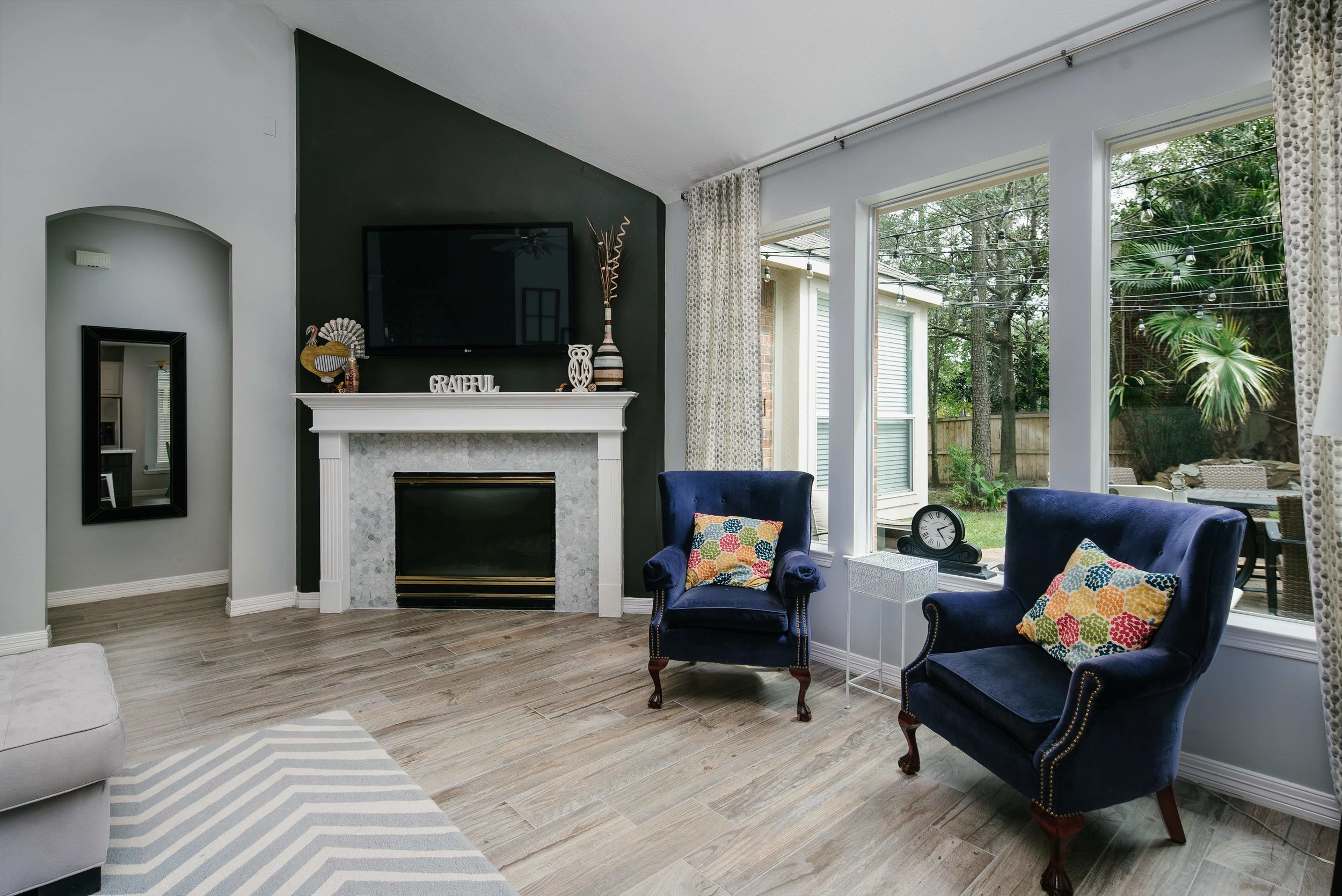 This living room is brought to life with these large elegant windows, the woodfloor tile, and the beautifully tiled fireplace.