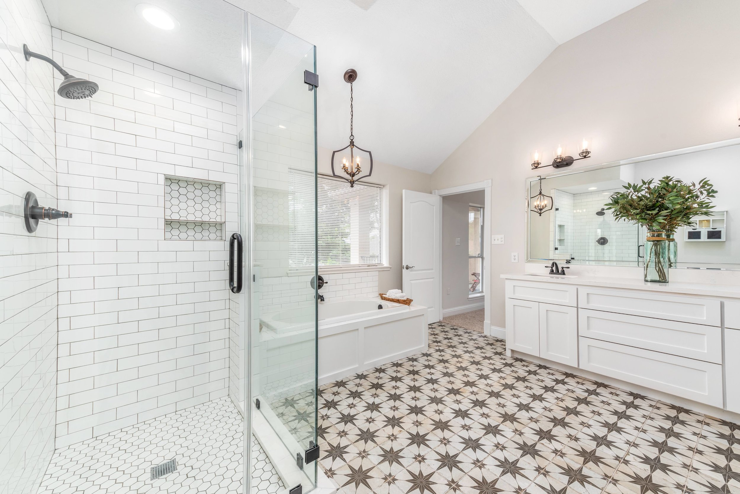 Stunning farmhouse master bathroom remodel. This bathroom features a frameless glass shower, antiqued Spanish tile, subway tile, quartz countertops, and bright natural lighting.