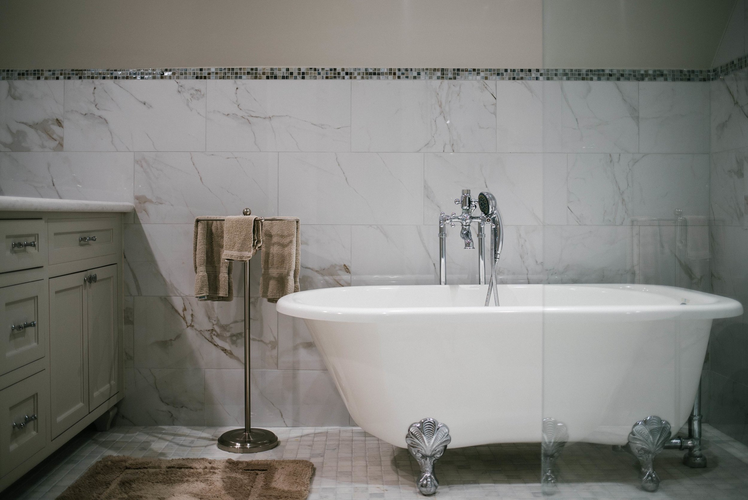 Stunning master bathroom remodel! Clawfoot bathtub, frameless walk in shower, intricate tile border, grey and beige tile, shaker style cabinets, paint.