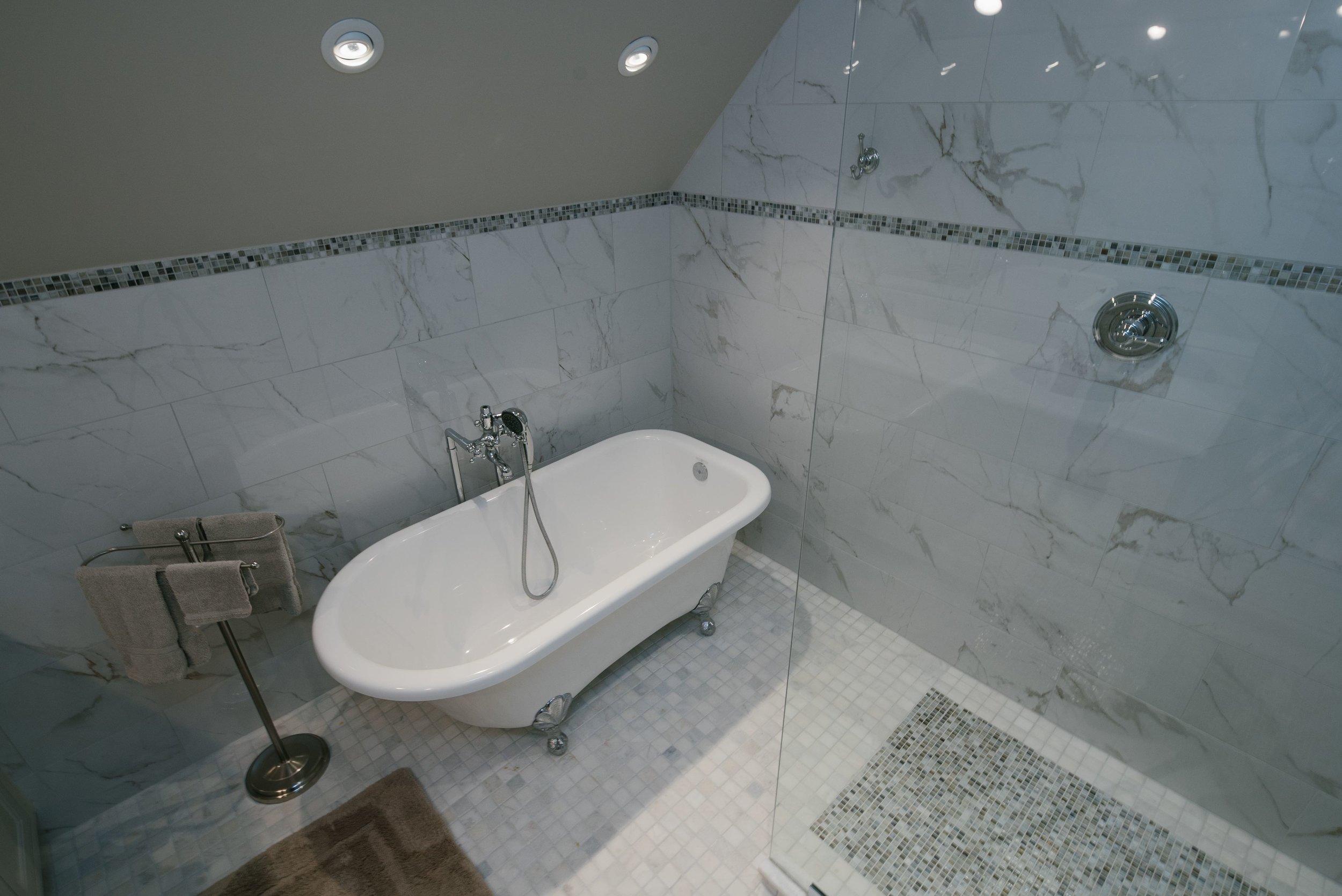 Walk in frameless glass shower, rain shower head, tile detail border, grey tile, marble tile, tile rug, paint, clawfoot bathtub.