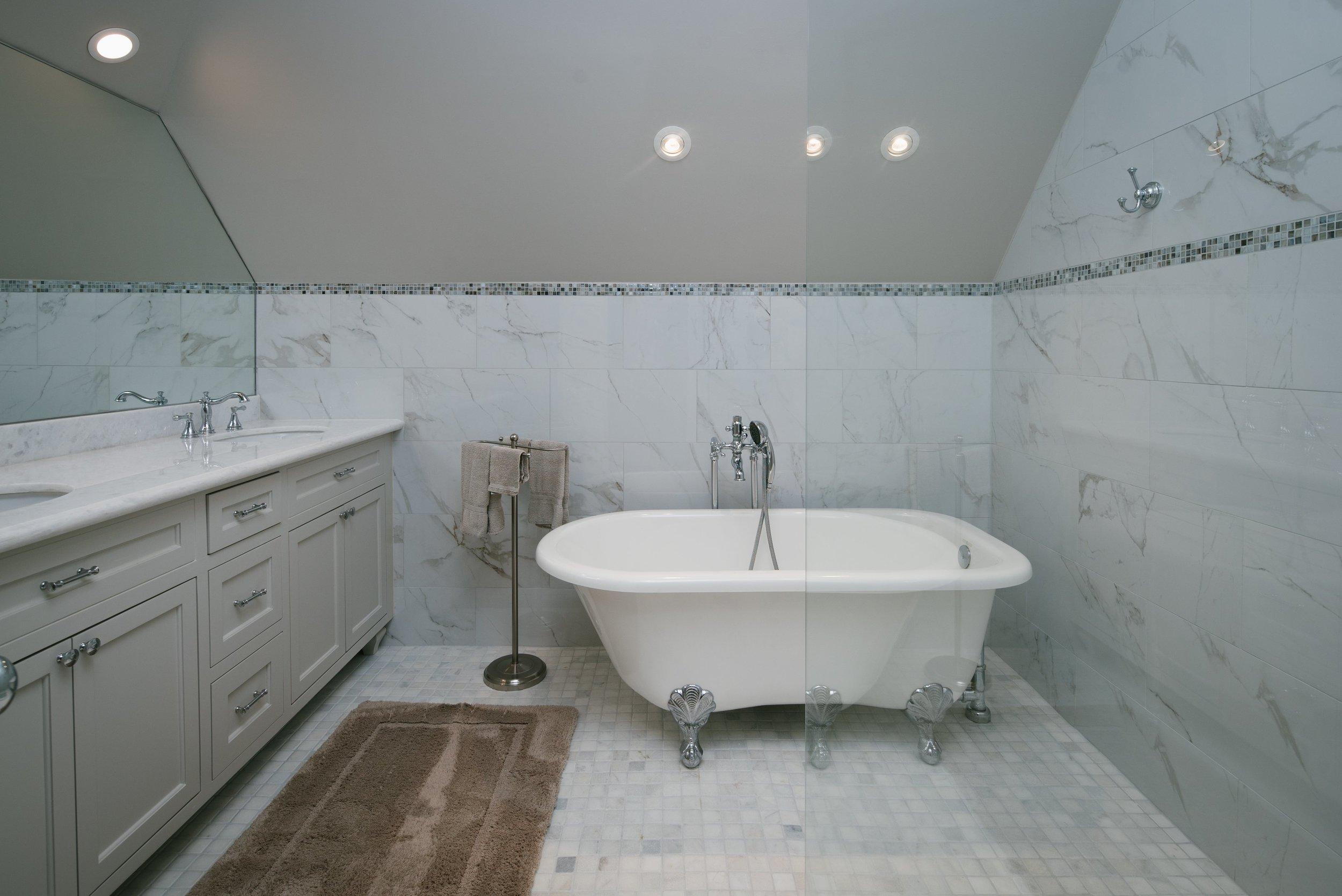 Clawfoot bathtub, frameless mirror, shaker style cabinets, quartz countertops, white countertops, marble tile, grey tile, frameless walk-in shower, glass shower, elegant bathroom.