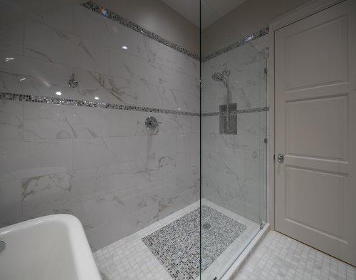Intricate tile rug, tile with decorative border, hand held shower head, frameless glass, walk-in shower, marble tile, grey tile, white tile.