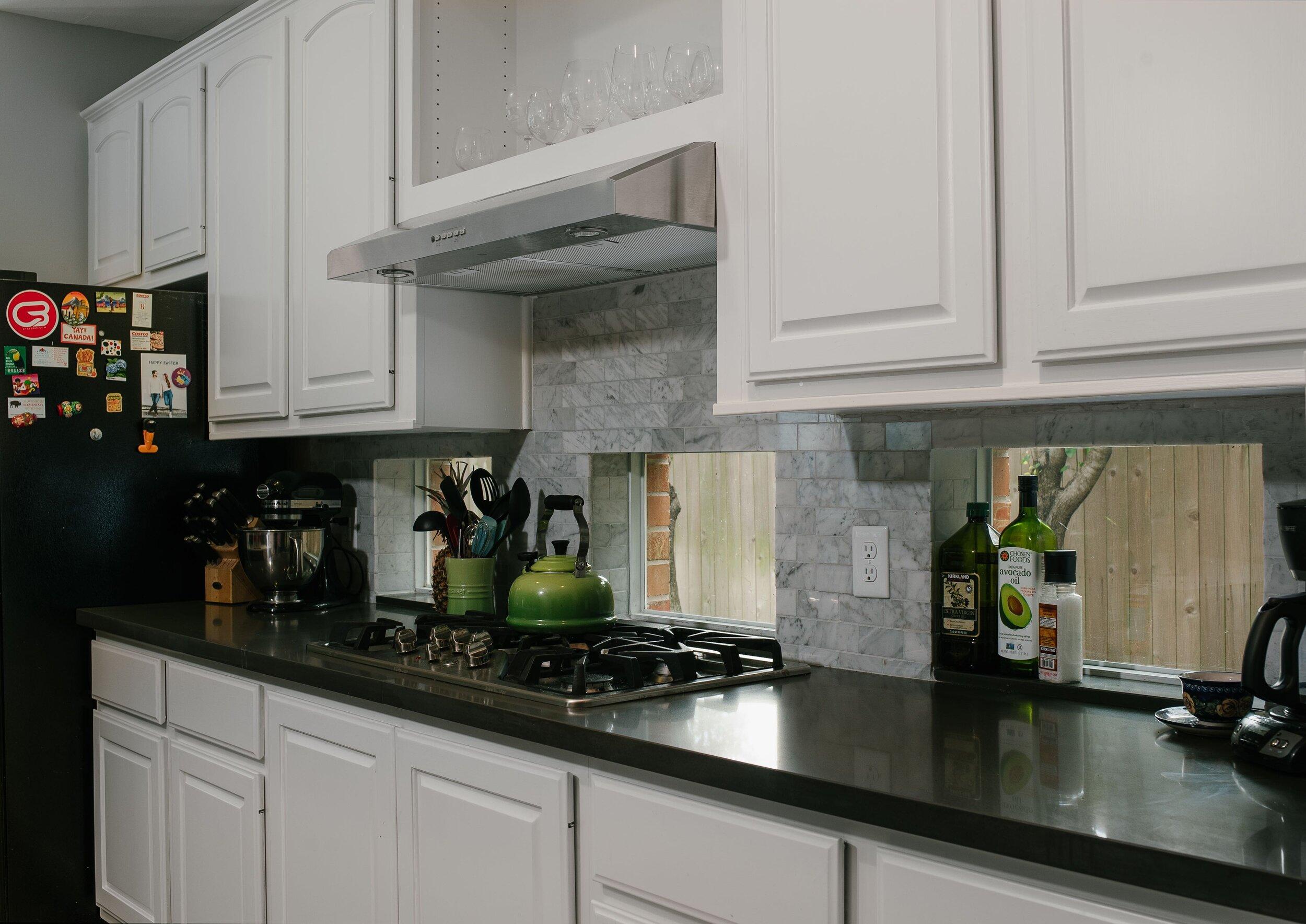 Grey backsplash tile, kitchen windows, black quartz countertops, stovetop, white cabinets. Stunning kitchen remodel.