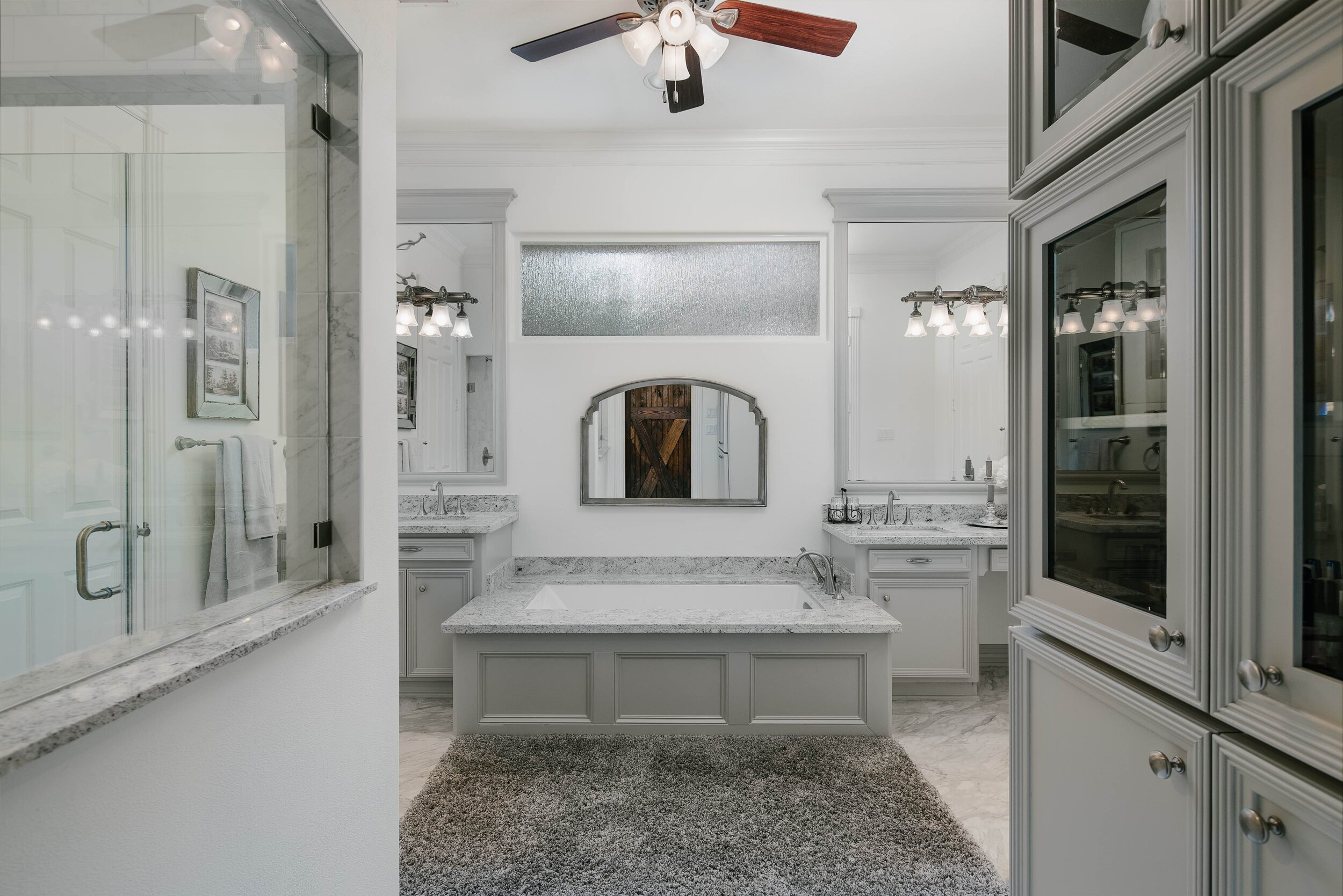 Gorgeous master bathroom remodel. Farmhouse inspired, farm door, grey and white master bathroom. Frameless walk in shower, grey shower tile, undermount bathtub, soaking tub, jet tub, grey granite countertops, marble floor tile, great cabinets, frames mirror, undermount sinks.