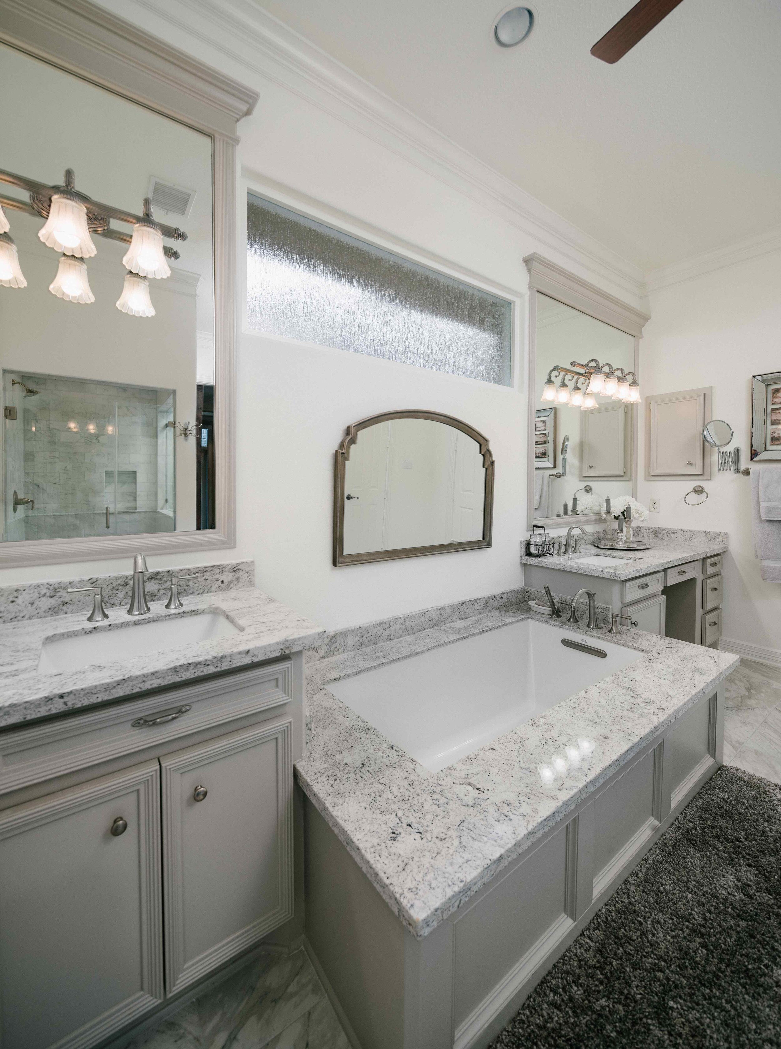 Master bathroom vanity, undermount bathtub, tub, undermount sink, soaking tub, frameless mirror, his and hers vanities, grey bathroom inspiration, grey bathroom, carrara marble tile, grey rug, grey paint, greige bathroom, greige paint, grey bathroom cabinets.