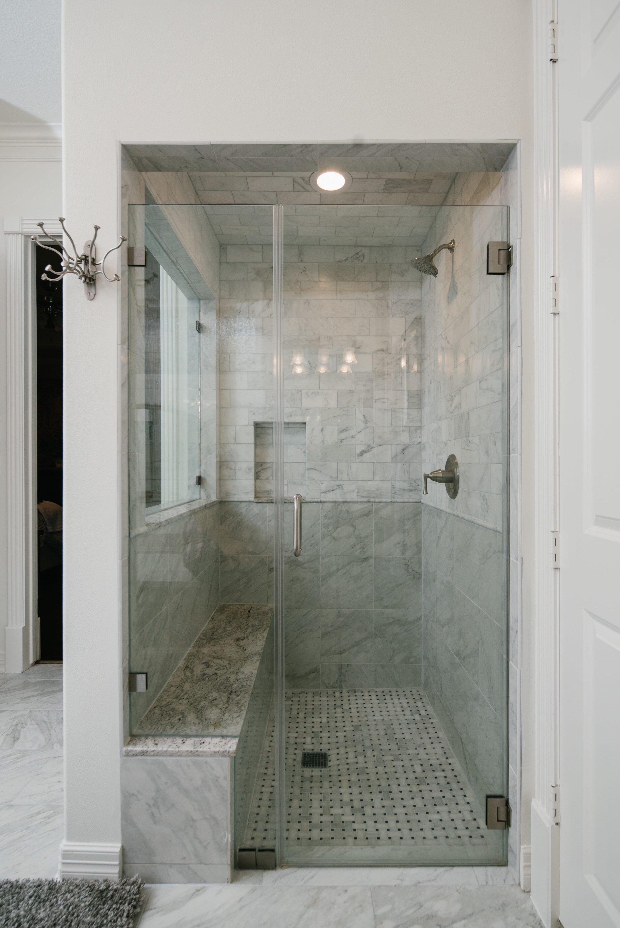 Walk-in frameless shower, glass, shower bench seat, shampoo niche, carrara marble tile, basketweave tile, grey and white carrara tile, shower remodel, dream shower, grey shower, shower inspiration.