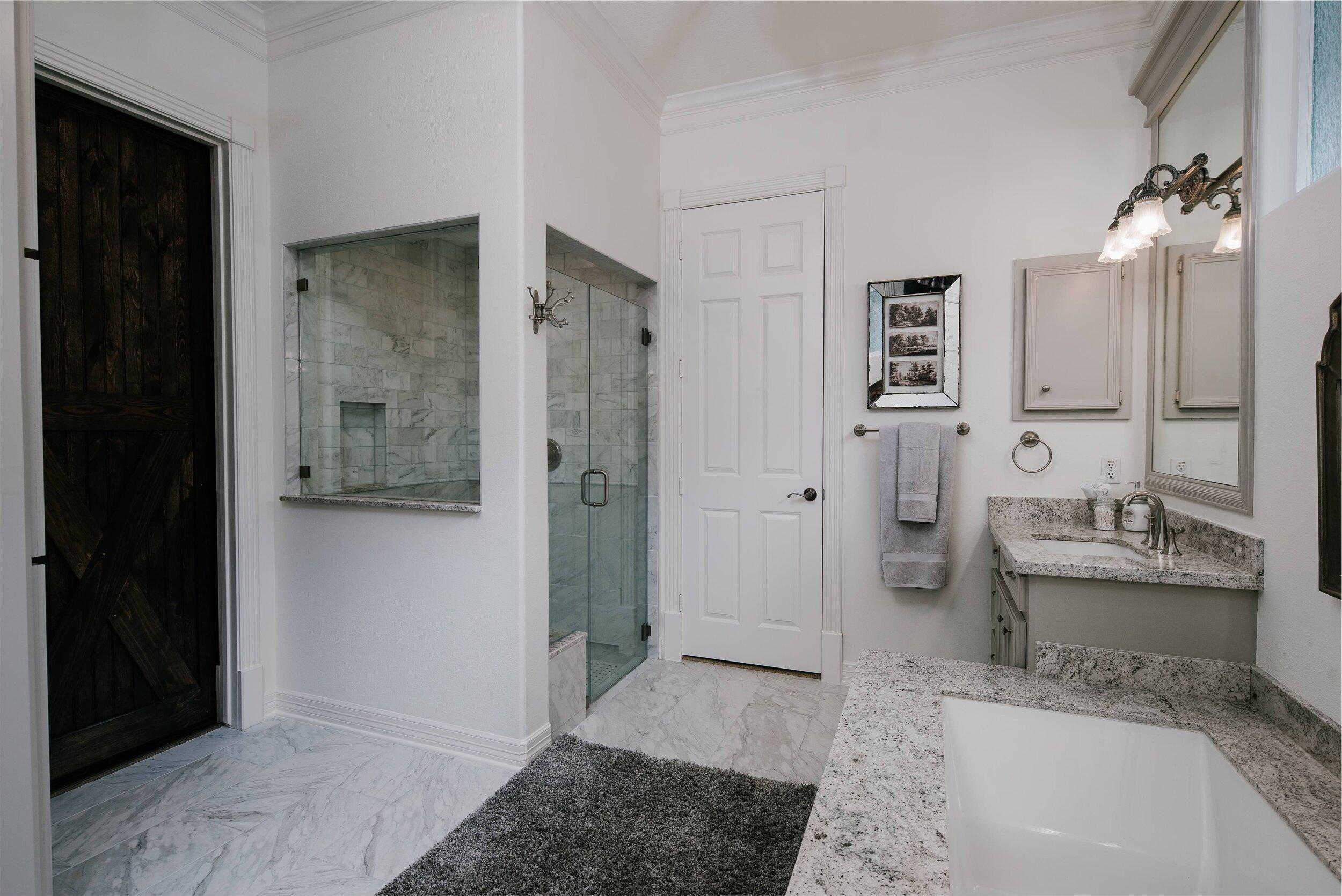 Elegant bathroom remodel, bathroom renovation, master bathroom inspiration, grey bathroom, undermount sink, undermount bathtub, granite countertops, carrara marble floors, white bathtub, white and grey bathroom.