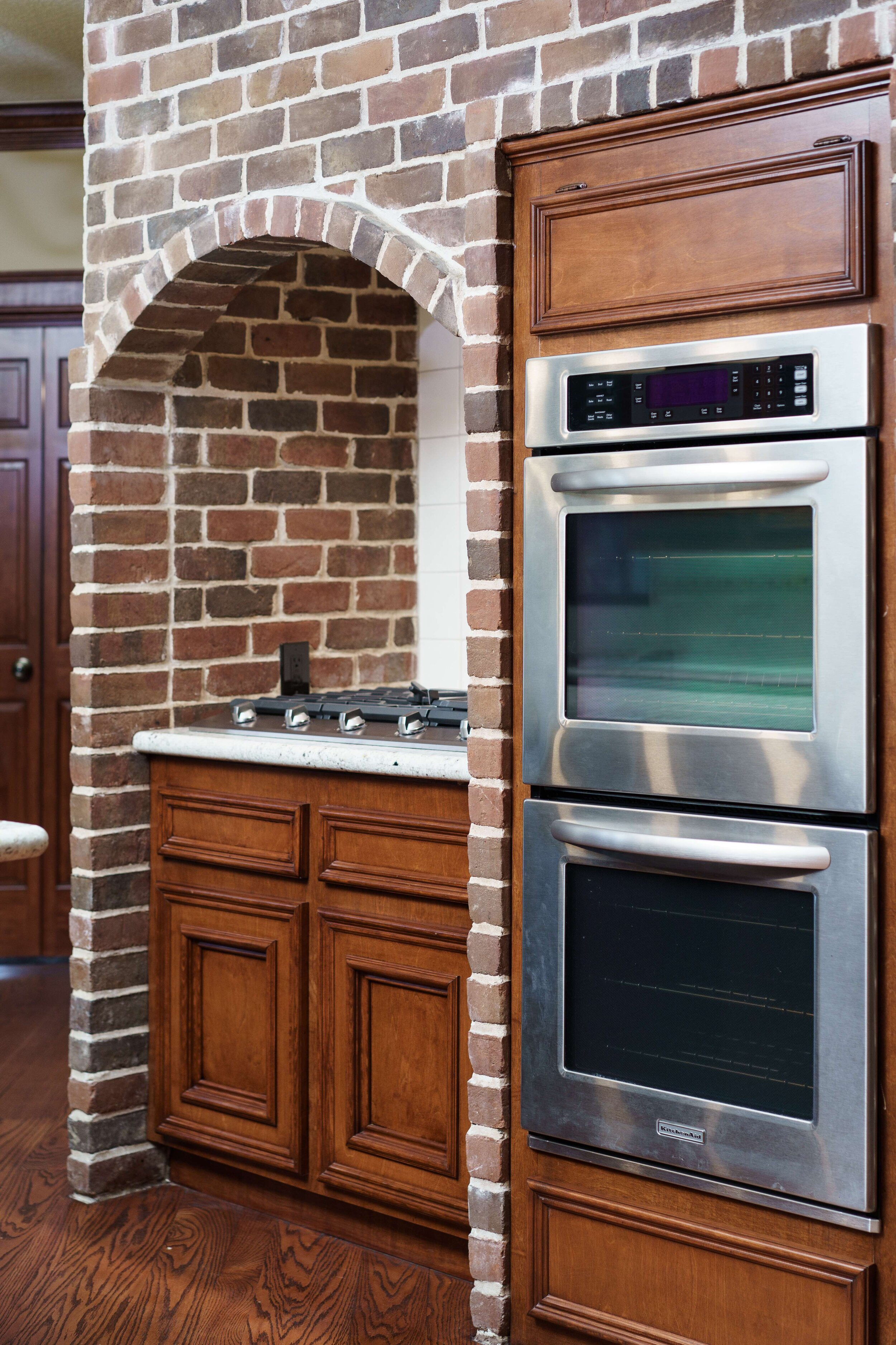 Brick accent wall in kitchen renovation. Stainless steel appliances, stainless steel gas cooktop, wood stained cabinets, oak wood floor.
