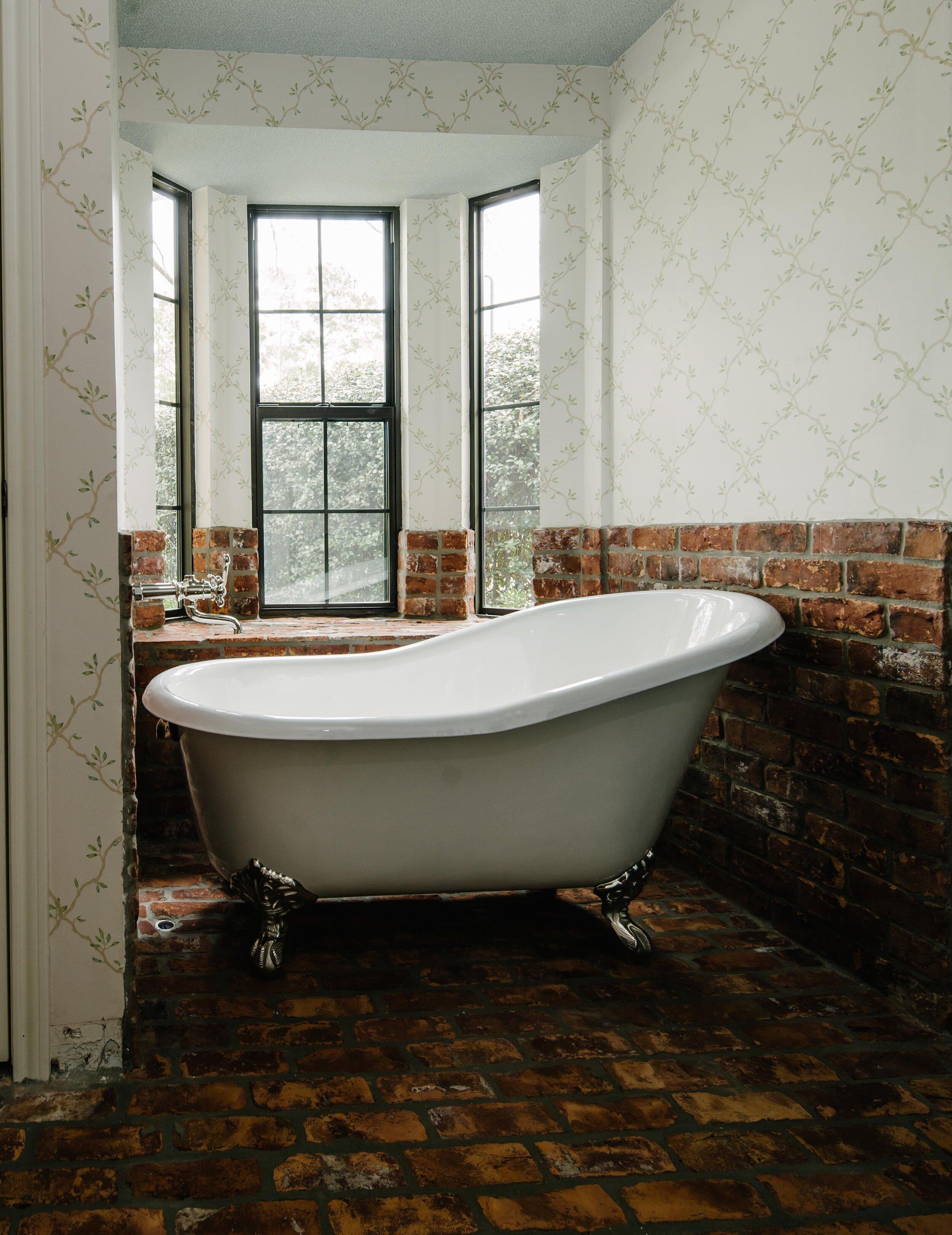 Claw foot bathtub, free standing bathtub, rustic brick floor, intricate wall papering, master bathroom renovation, master bathroom remodel.