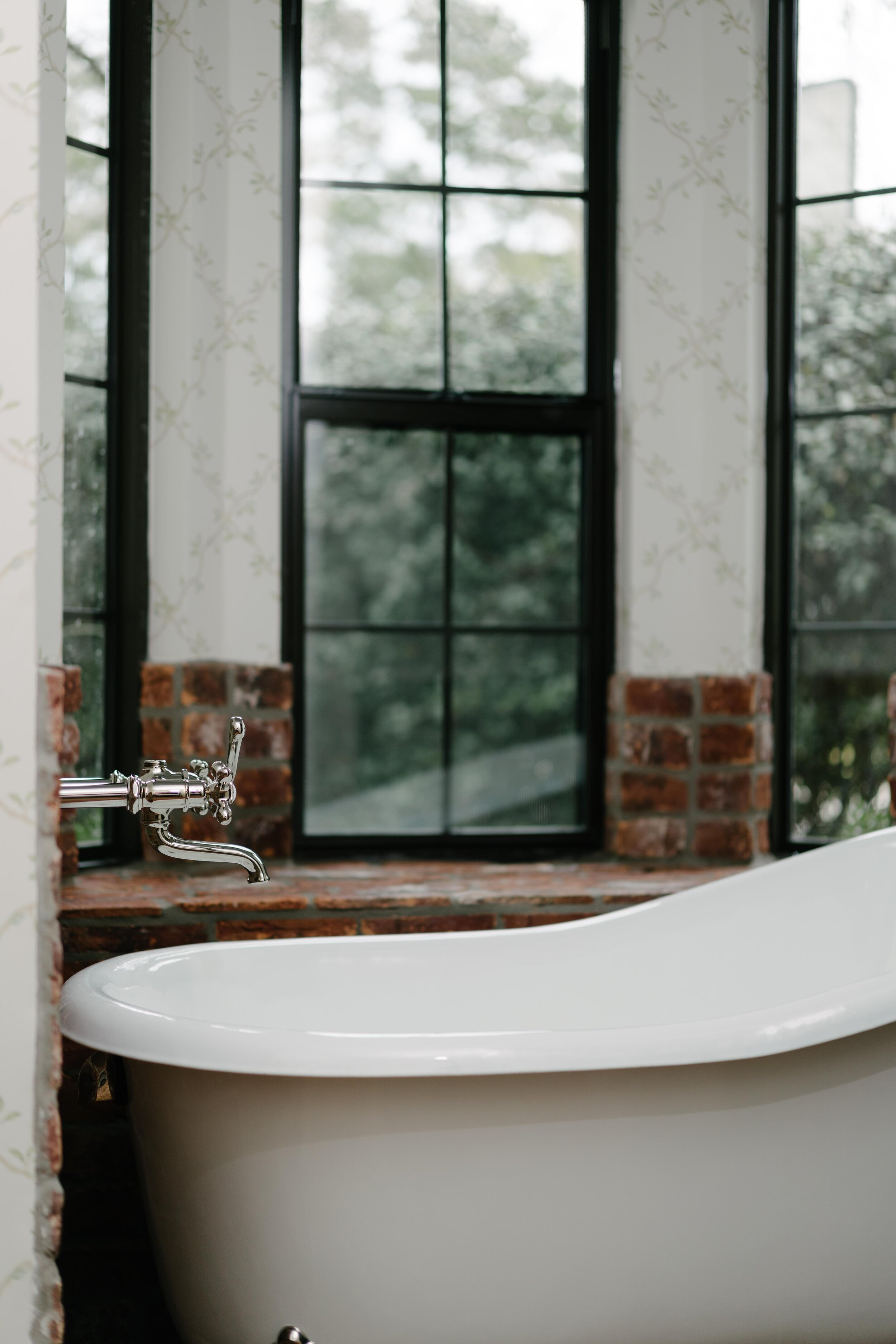 Stunning master bathroom renovation. Featuring free standing bathtub, clawfoot bathtub with wall mount stainless steel faucet. Farmhouse master bathroom renovation.
