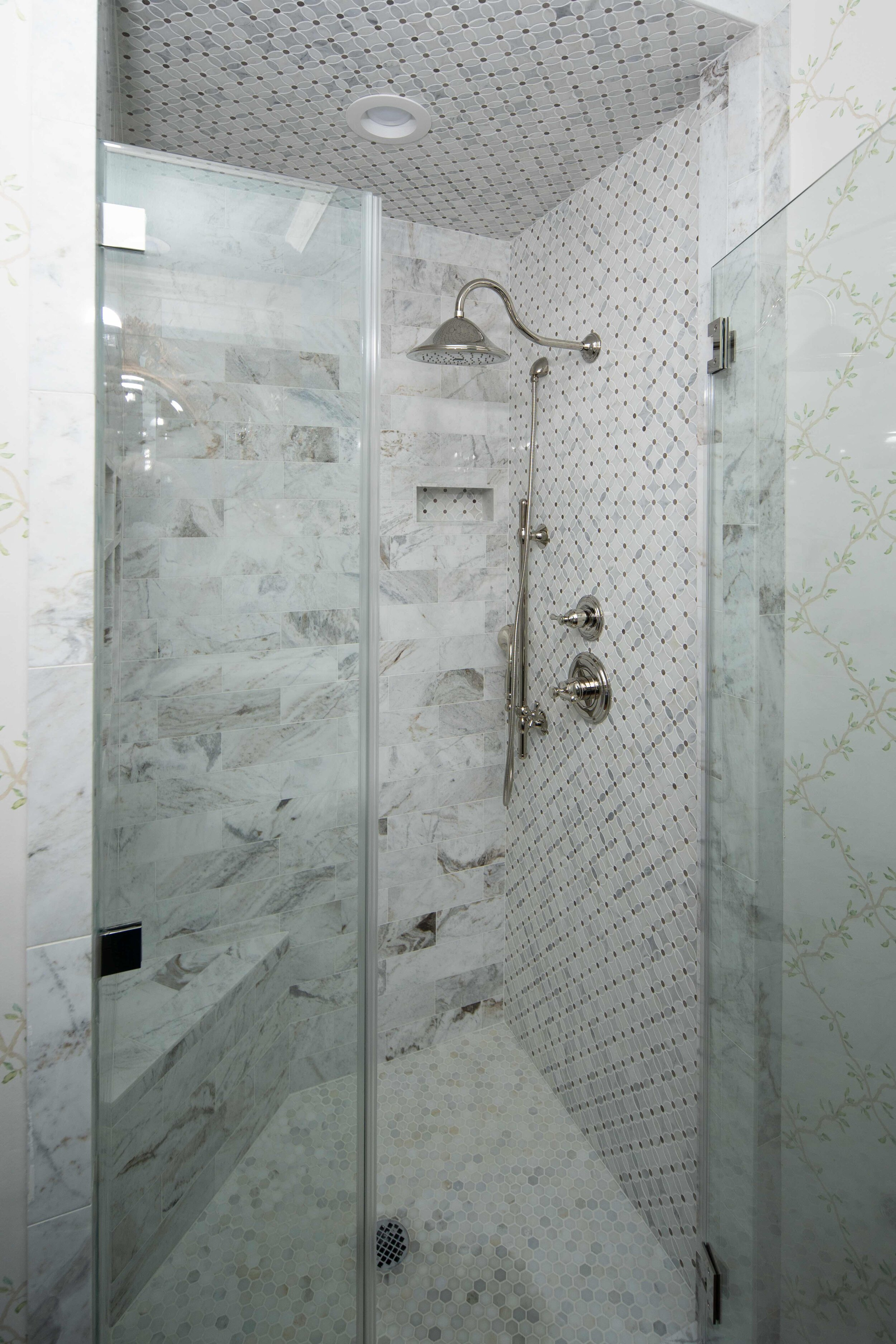 White and grey carrara marble shower renovation. Shower remodel. This walk in shower features a hexagon carrara marble tile rug on the the shower floor. Decorative marble mosaic tile accent wall in shower with. Frameless glass walk in shower is finished with stainless steal finishings. Multiple shampoo niches for convenient storage of shower items.