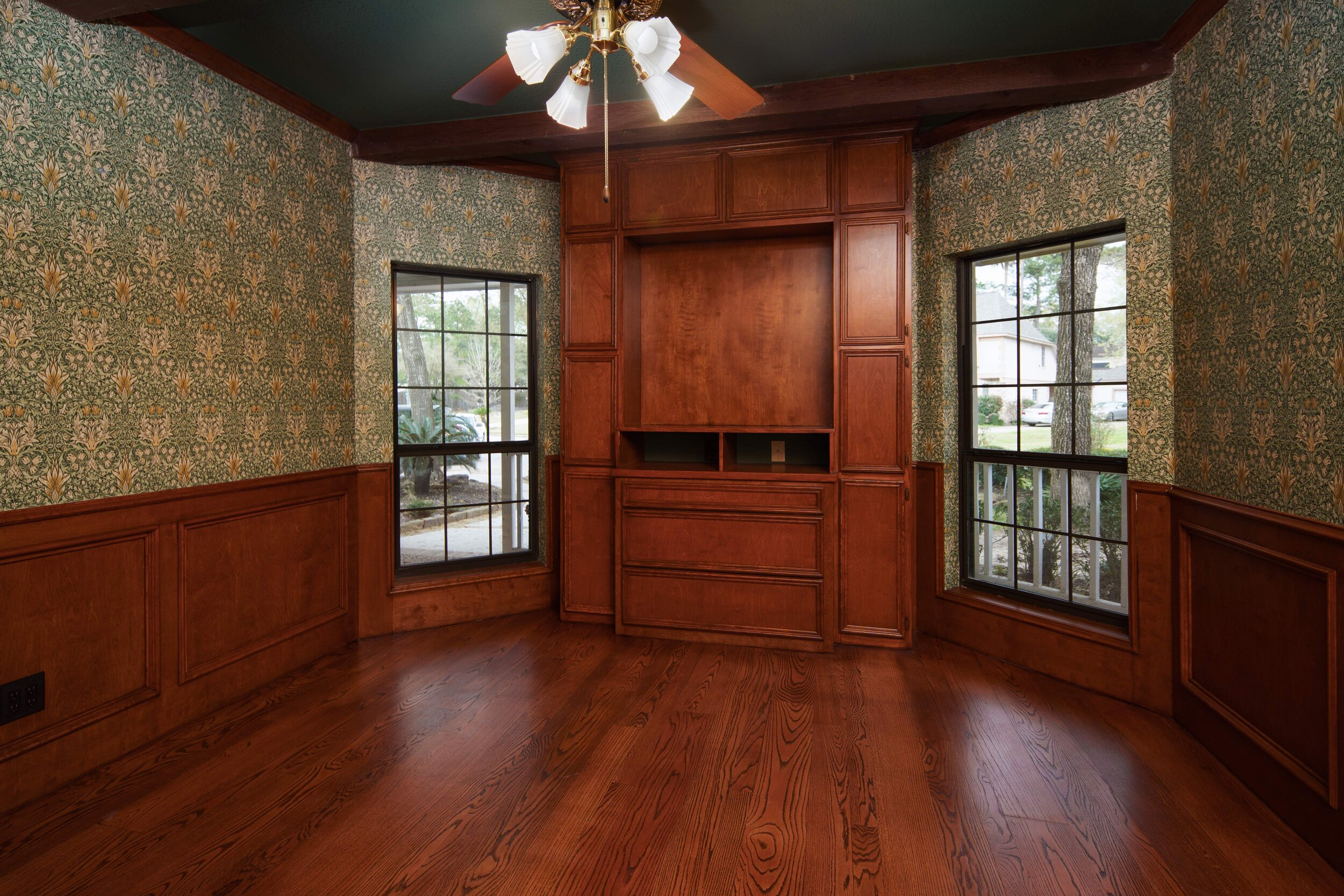 Full home restoration, full home renovation. The room features, custom built in cabinets, oak floors, wood stained trim. Office study renovation. intricate wall paper design perfect for this study.