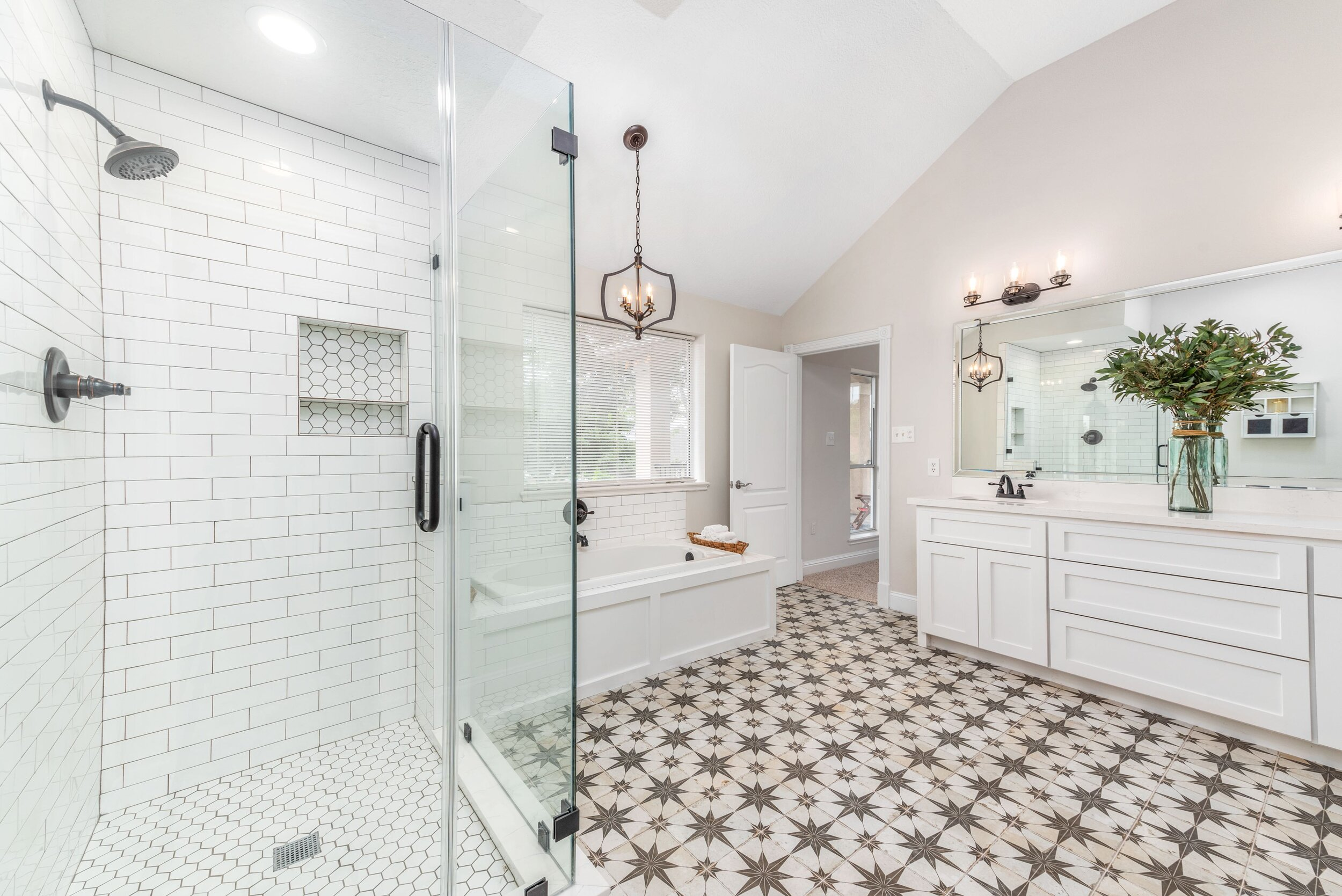 This stunning master bathroom was an amazing project. This room was completely transformed from two rooms into one to include a frameless walk in shower, custom shaker style cabinets, encaustic tile floor, spanish tile floor, subway tile with dark grout. The shower floor features a hexagon subway tile, with tile rubbed bronze finish. Brand new paint, fixtures, and bathtub.