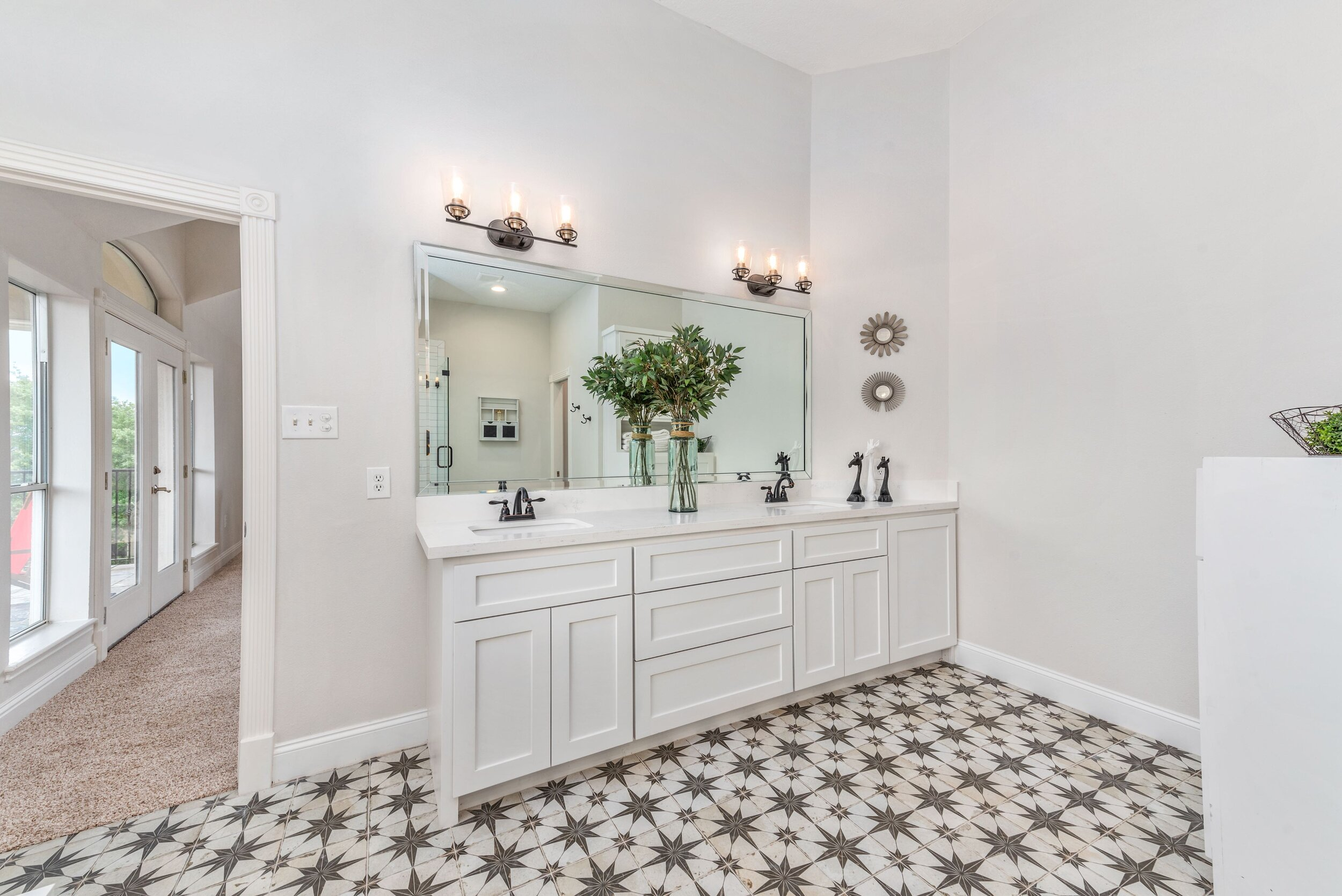 Master bathroom renovation, frameless mirror, his and hers vanities, his and hers sinks, farmhouse style lighting, encaustic tile floors, trim and base boards, shaker style cabinets.
