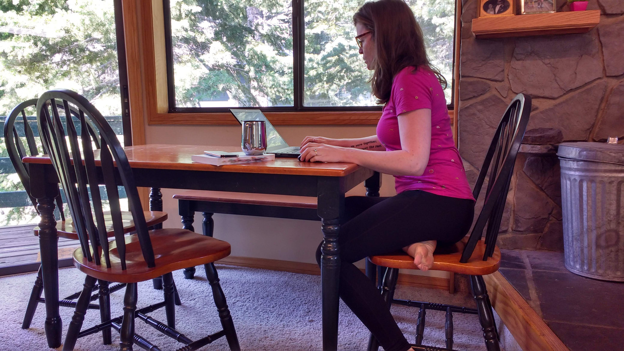 Image description: writer Charlotte Kaufman seated at a dining table with her right leg tucked under her left. She is looking at and typing on a laptop on the table, in front of a window with pine trees in the distance.