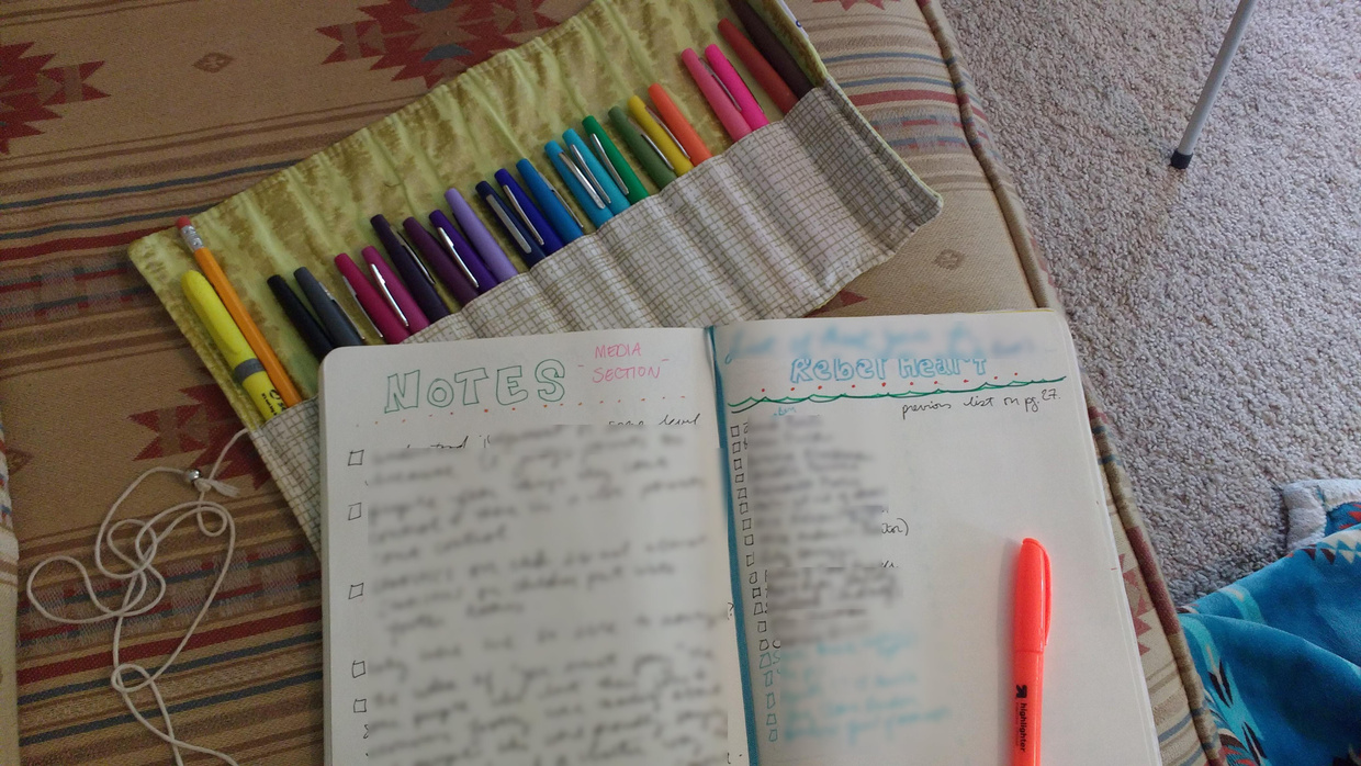 Image Description: an open bullet journal on a southwest-style couch cushion on top of a roll of markers organized to the colors of the rainbow. The left page of the journal says Notes - Media Section and the text of page is blurred. The right page says Rebel Heart and the rest of the text is blurred.