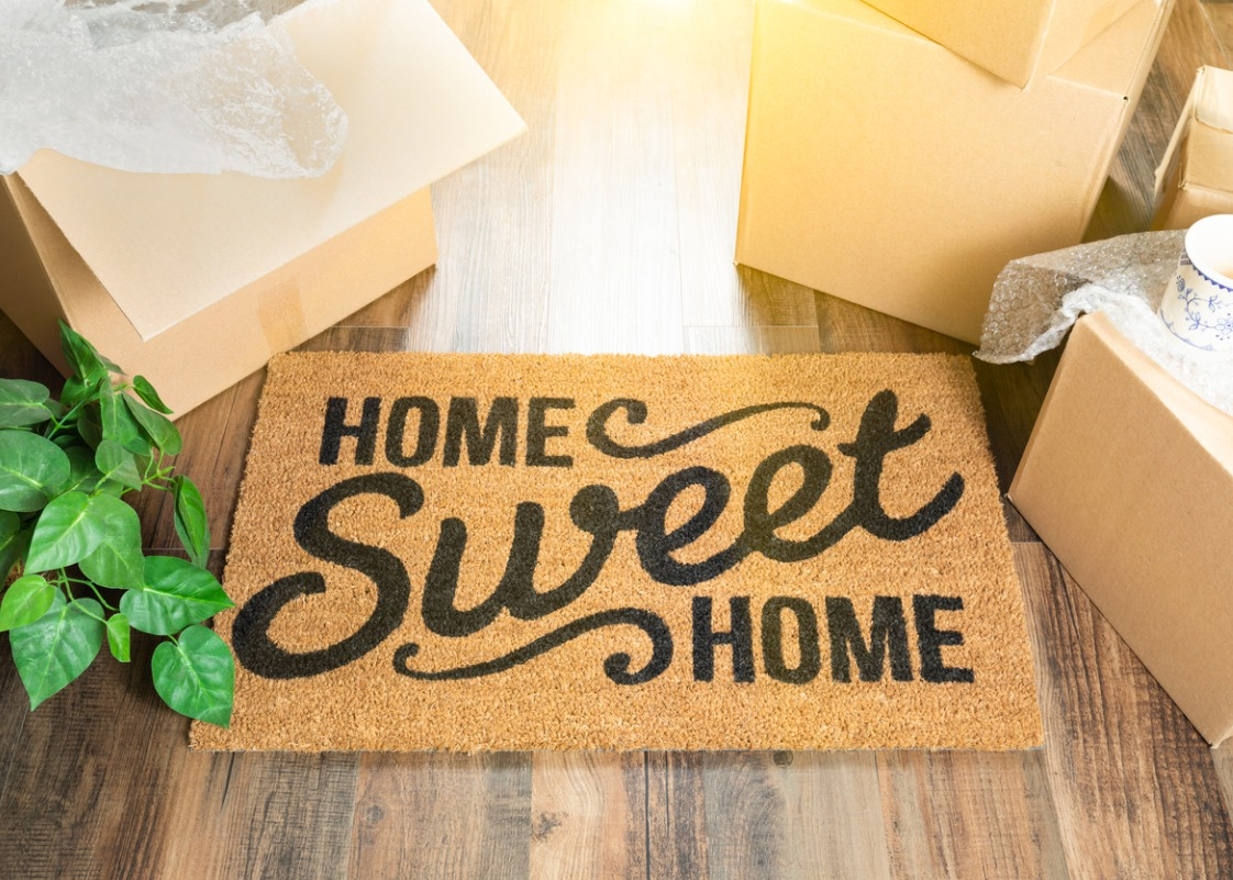 home-sweet-home-welcome-mat-and-moving-boxes-on-hard-wood-floor-picture-id962708926.jpg