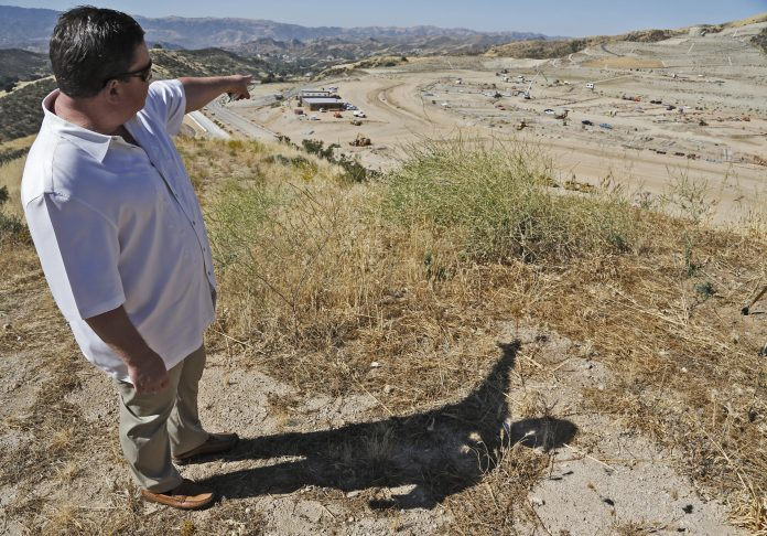 Project manager Randy Wrage points to where buildings and athletic fields will be completed by August 2019 at the site of the future Castaic High School during a media tour on Friday, June 16, 2017. Katharine Lotze/The Signal