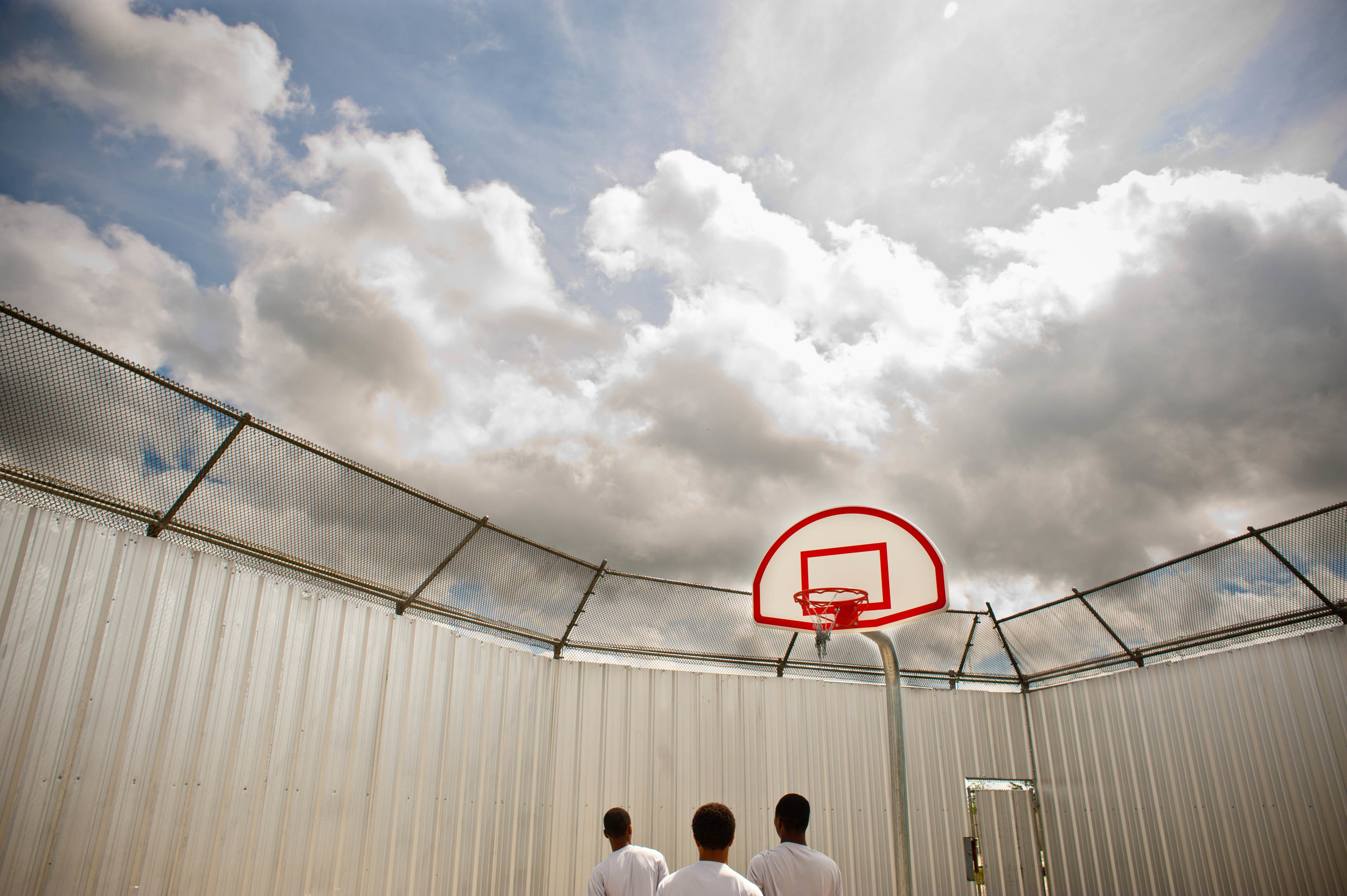 Teenage boys play basketball at the Youth Study Center juvenile detention facility in New Orleans, LA.
