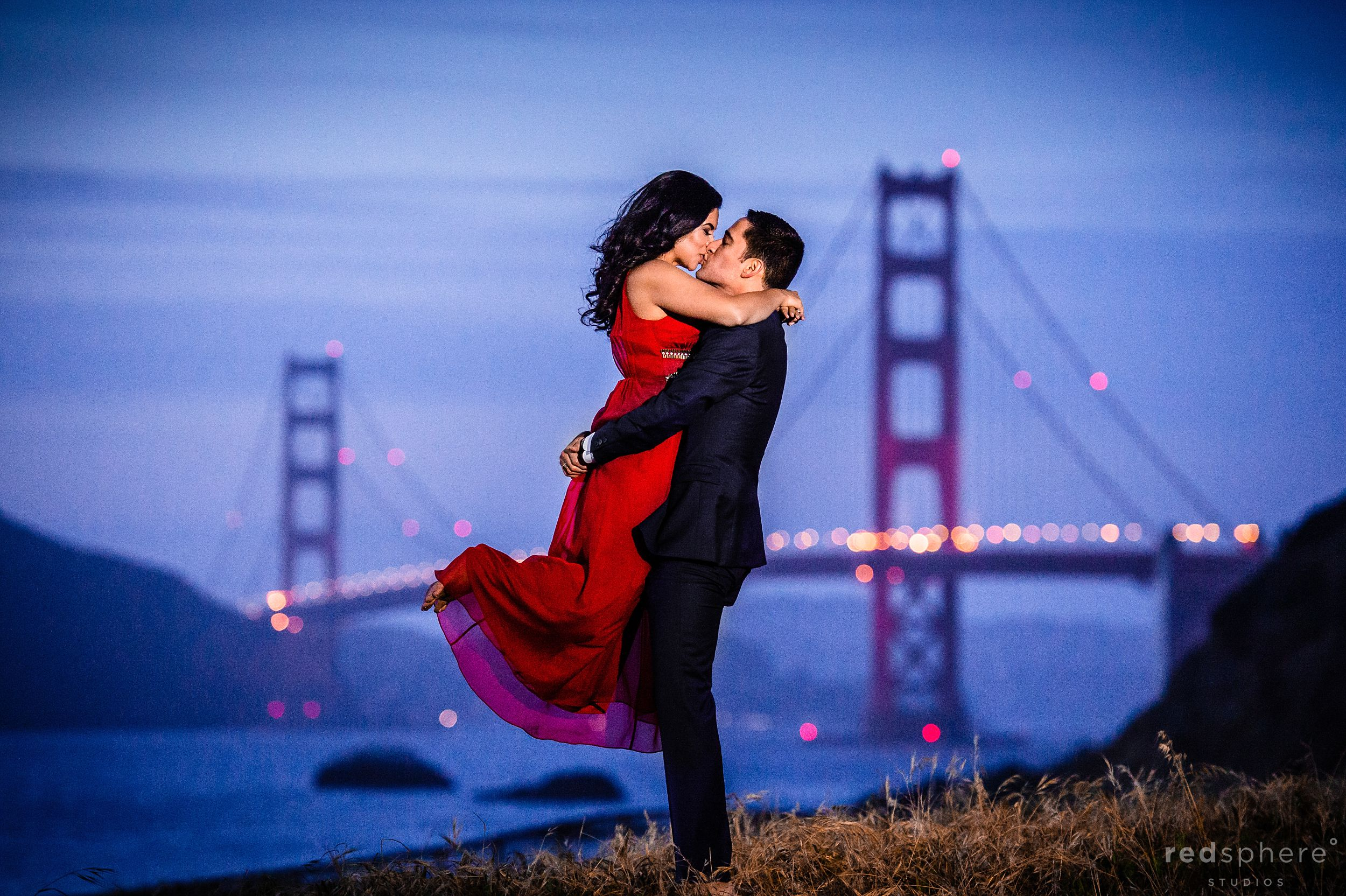 Couple Kiss at Baker Beach Engagement With Golden Gate Bridge in the Background
