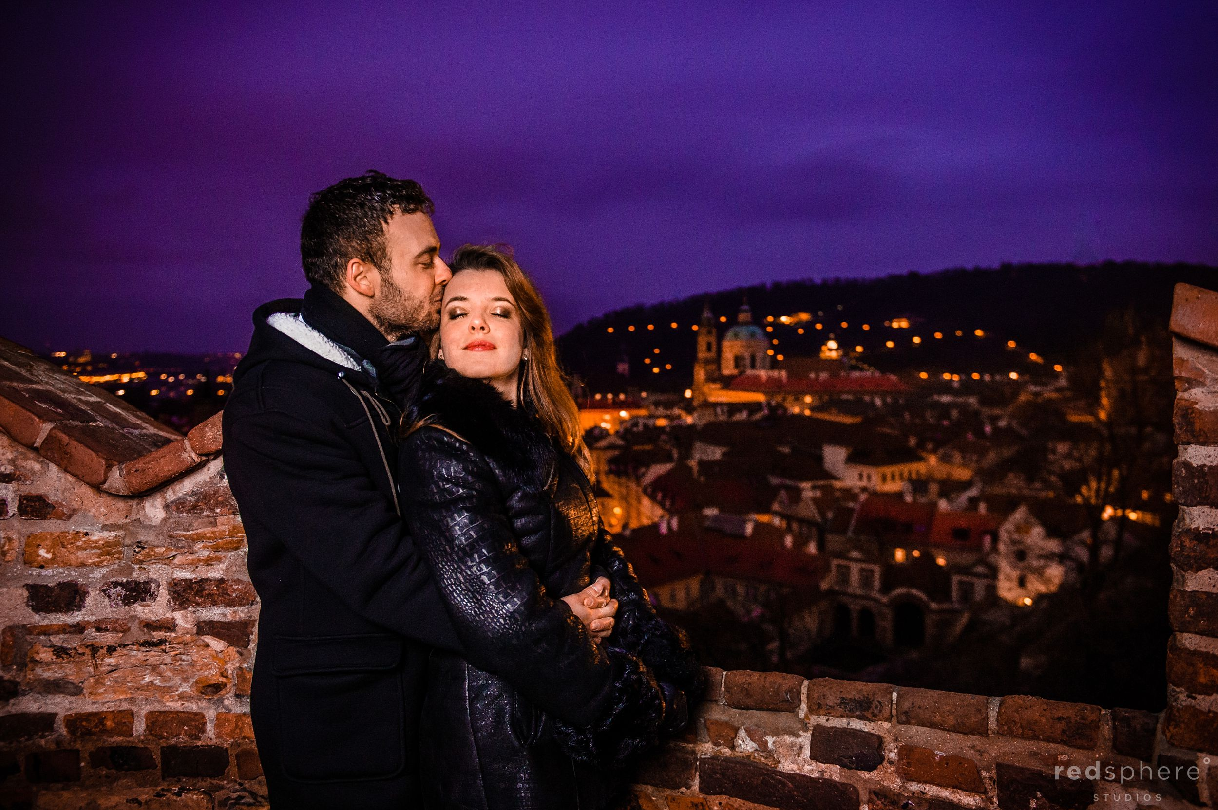 Couple Embrace During Winter Night at Prague Castle Engagement